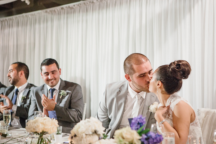 bride-groom-kiss-at-wedding-table