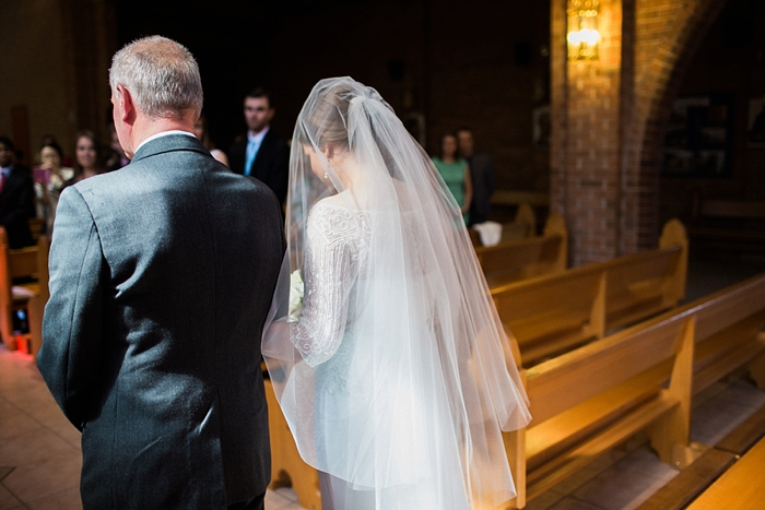 bride walking down the aisle in catholic ceremony