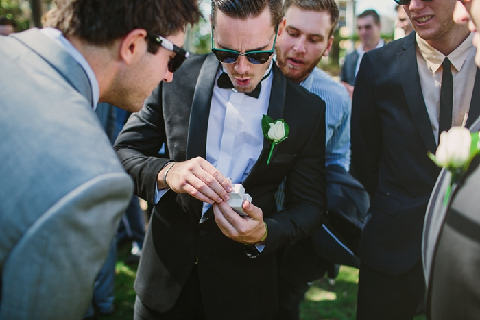 groomsmen look at wedding ring surprise