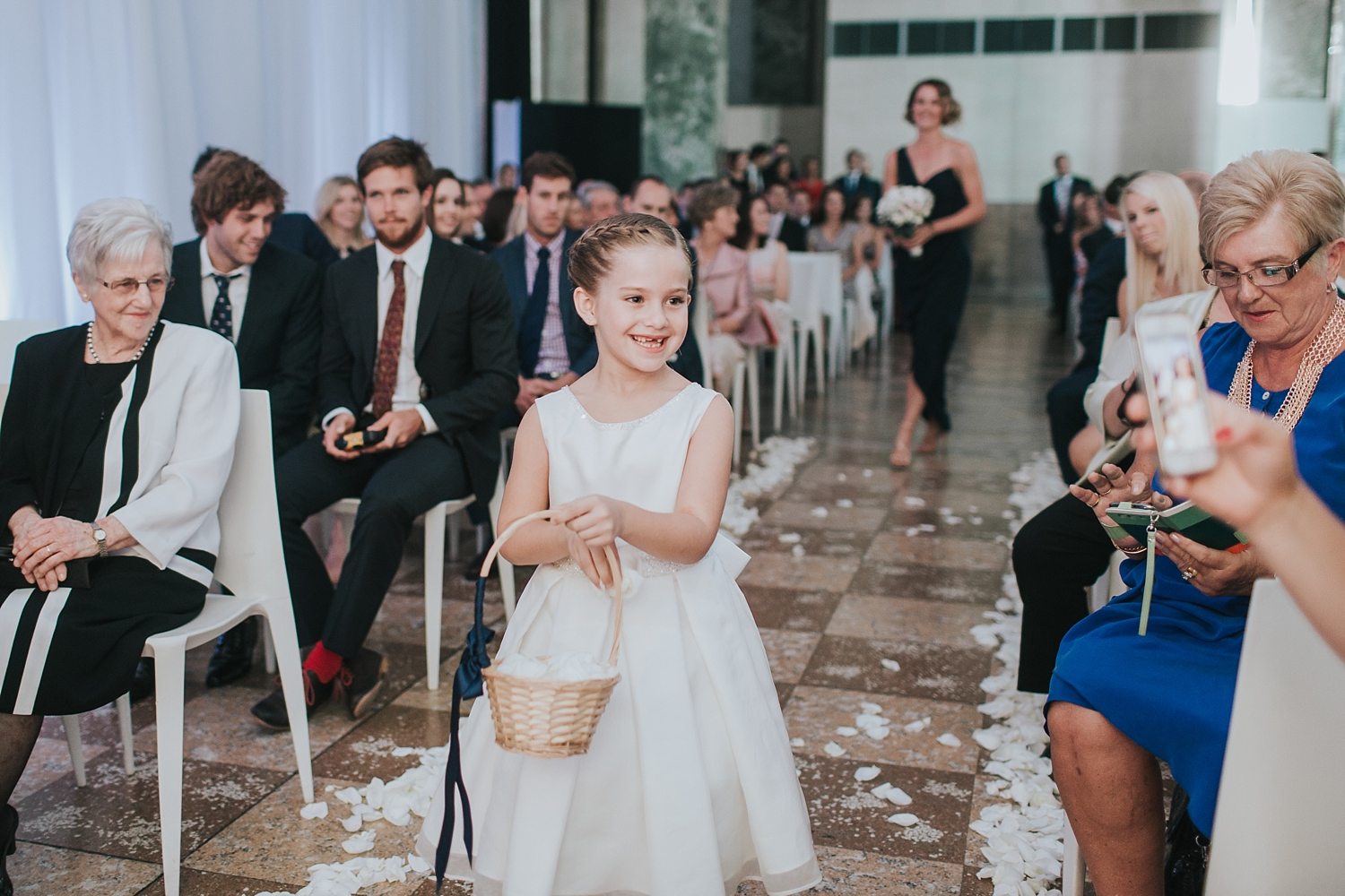 flower girl walking down the aisle at the mca