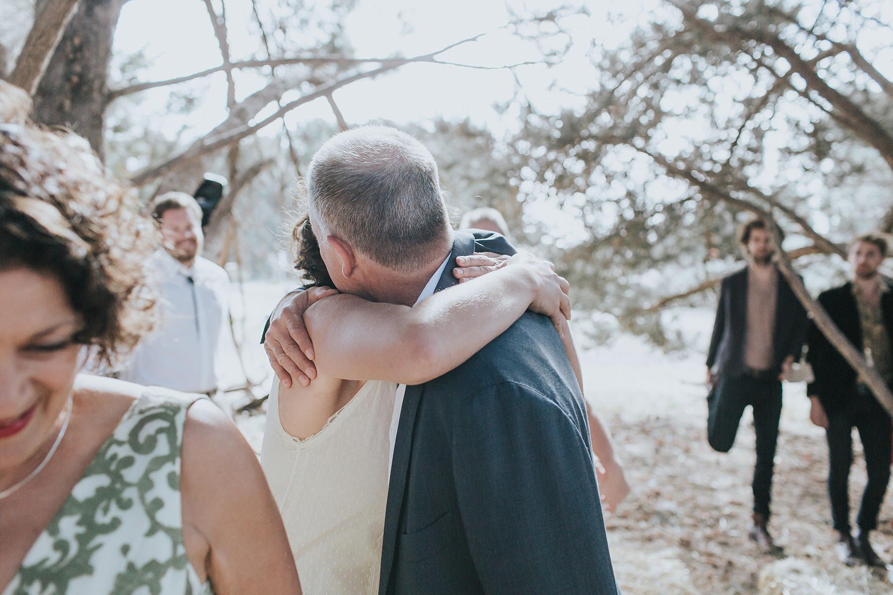 bride hugs her father during wedding ceremony
