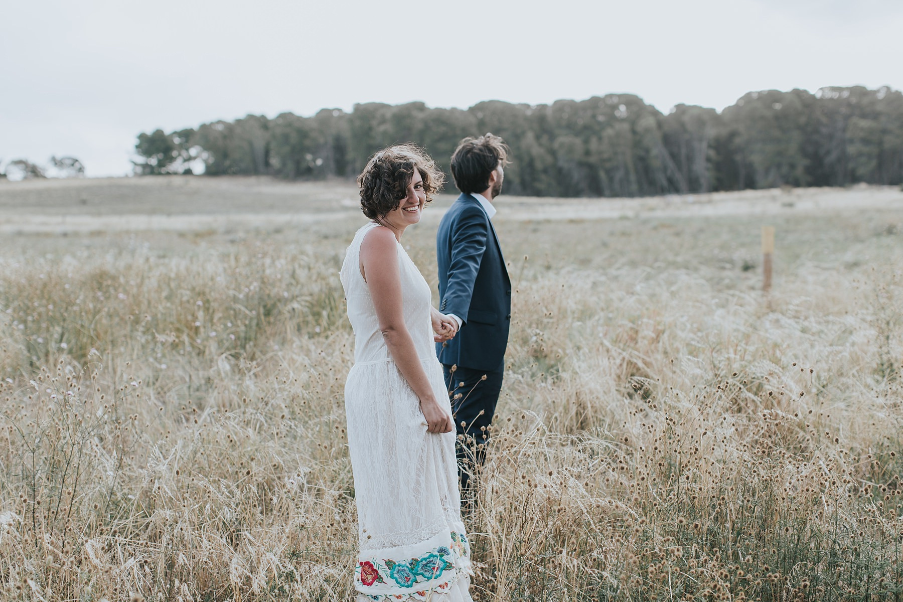 bride looks at camera as they walk into a field