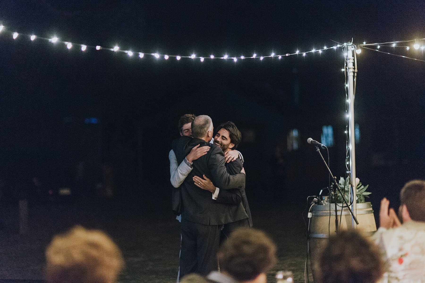 father of the bride being hugged by his new son in law