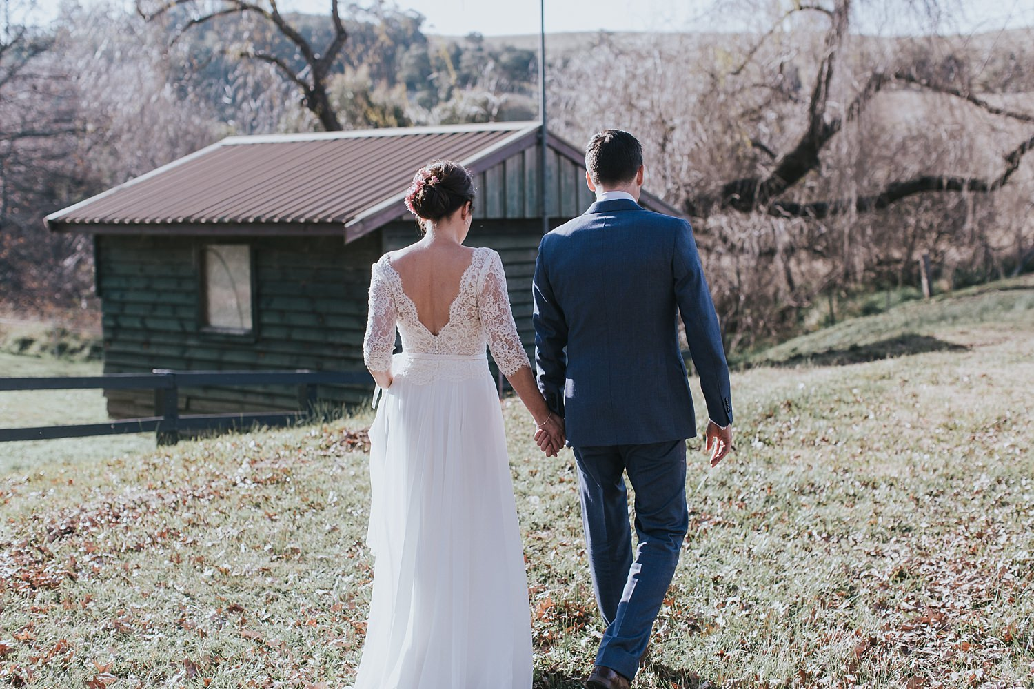 bride and groom walk into the field at bendooley estate