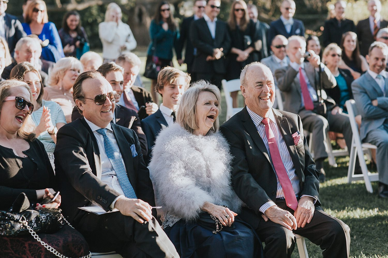 father and mother of the groom laughing during ceremony