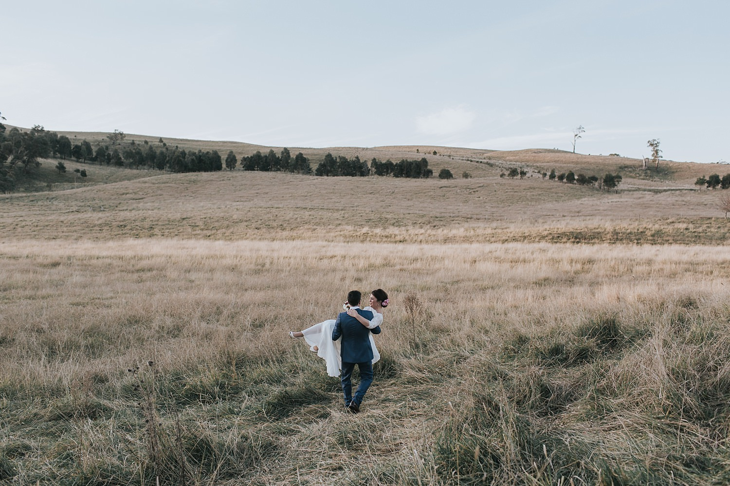 groom carries his bride into the fields at bendooley estate
