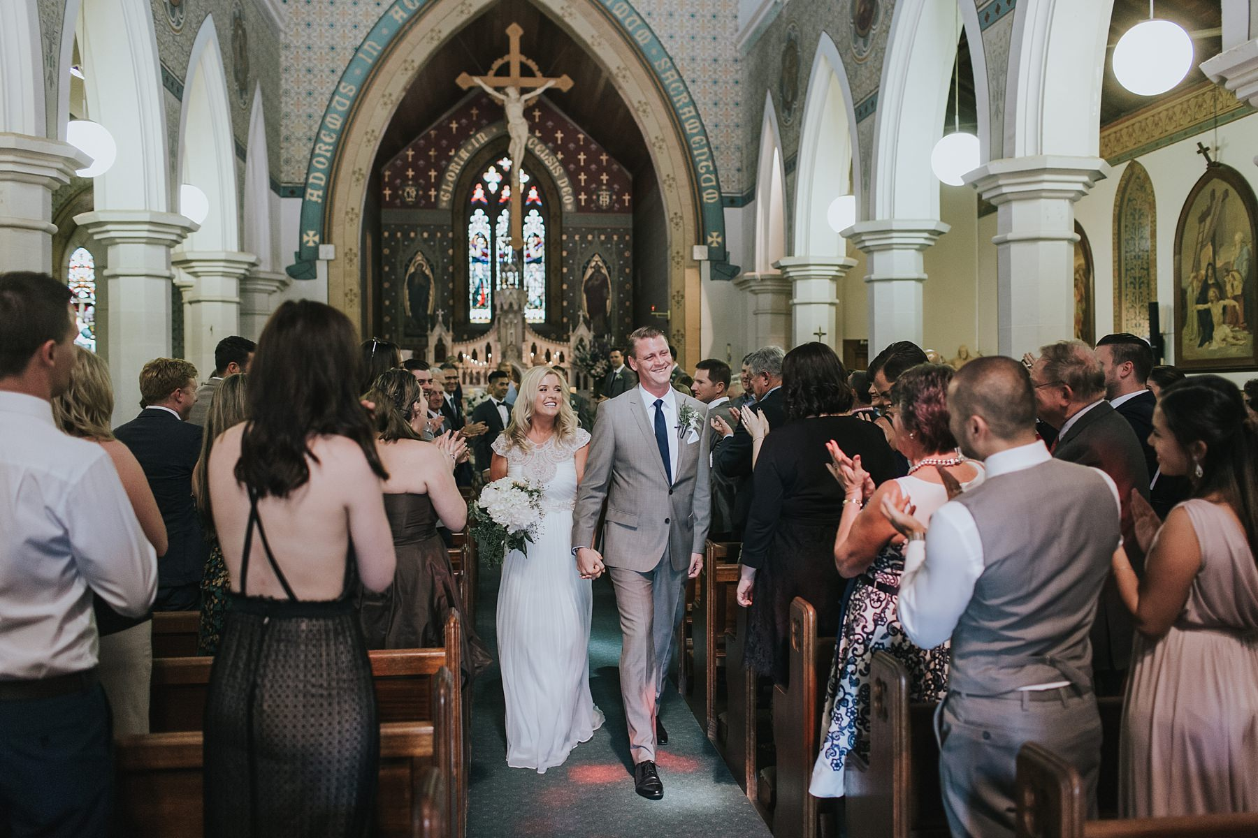 bride and groom walking down the aisle in catholic ceremony