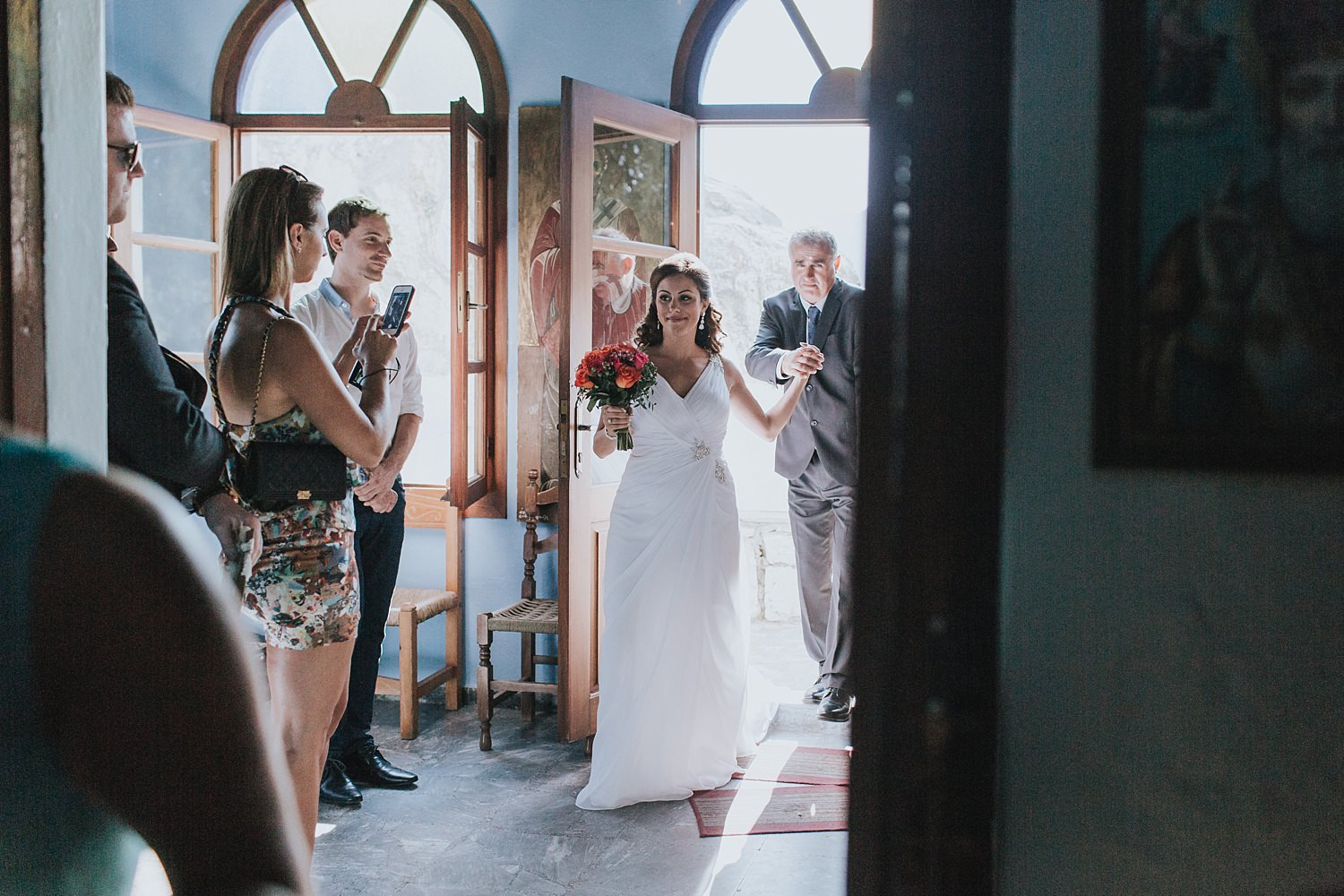 bride enters greek orthodox church for wedding
