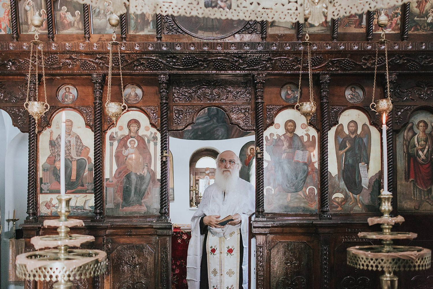 greek orthodox priest watches on from the sanctuary
