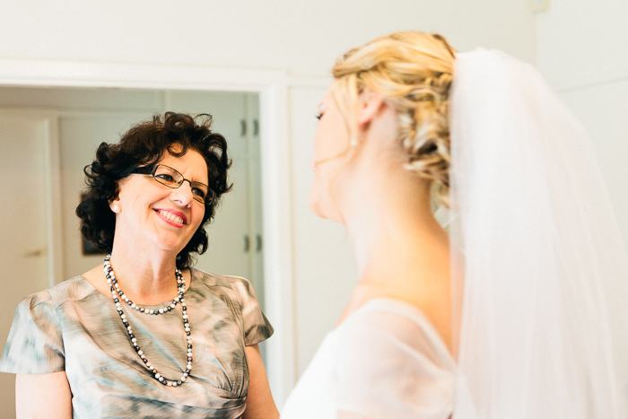 mother-of-the-bride-looks-at-daughter-in-her-dress