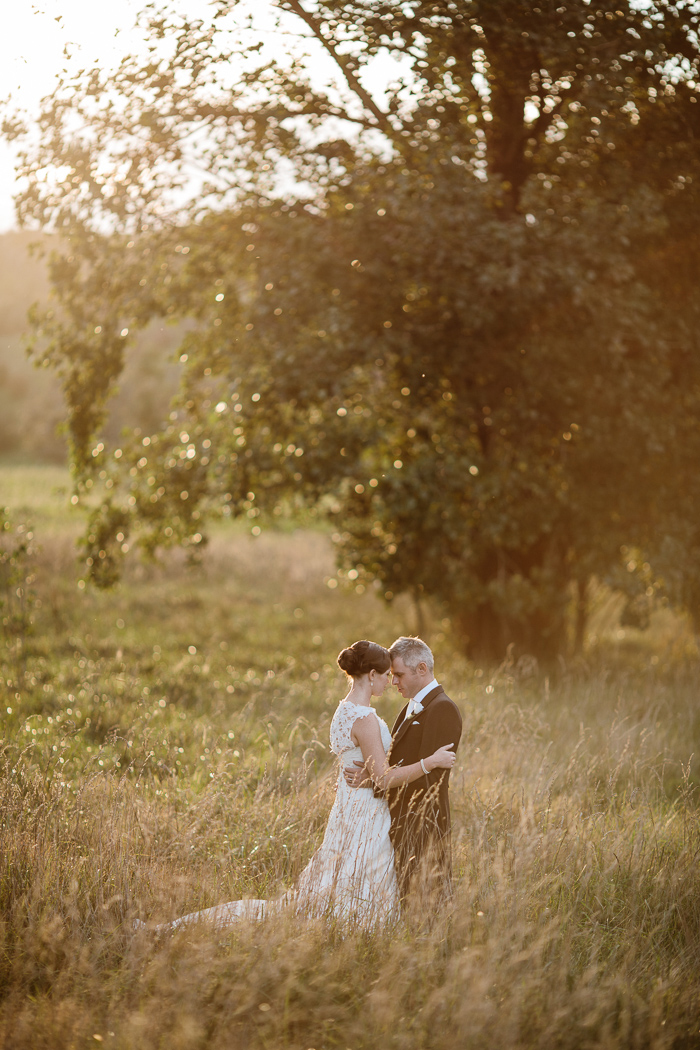bride-and-groom-in-open-field-sunset