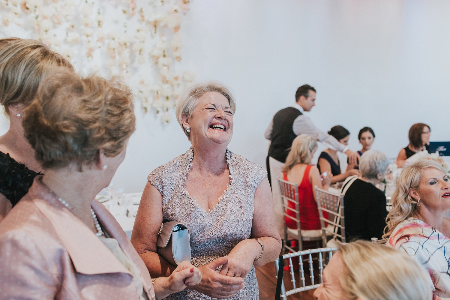 mother of the groom laughs with guests at the mca
