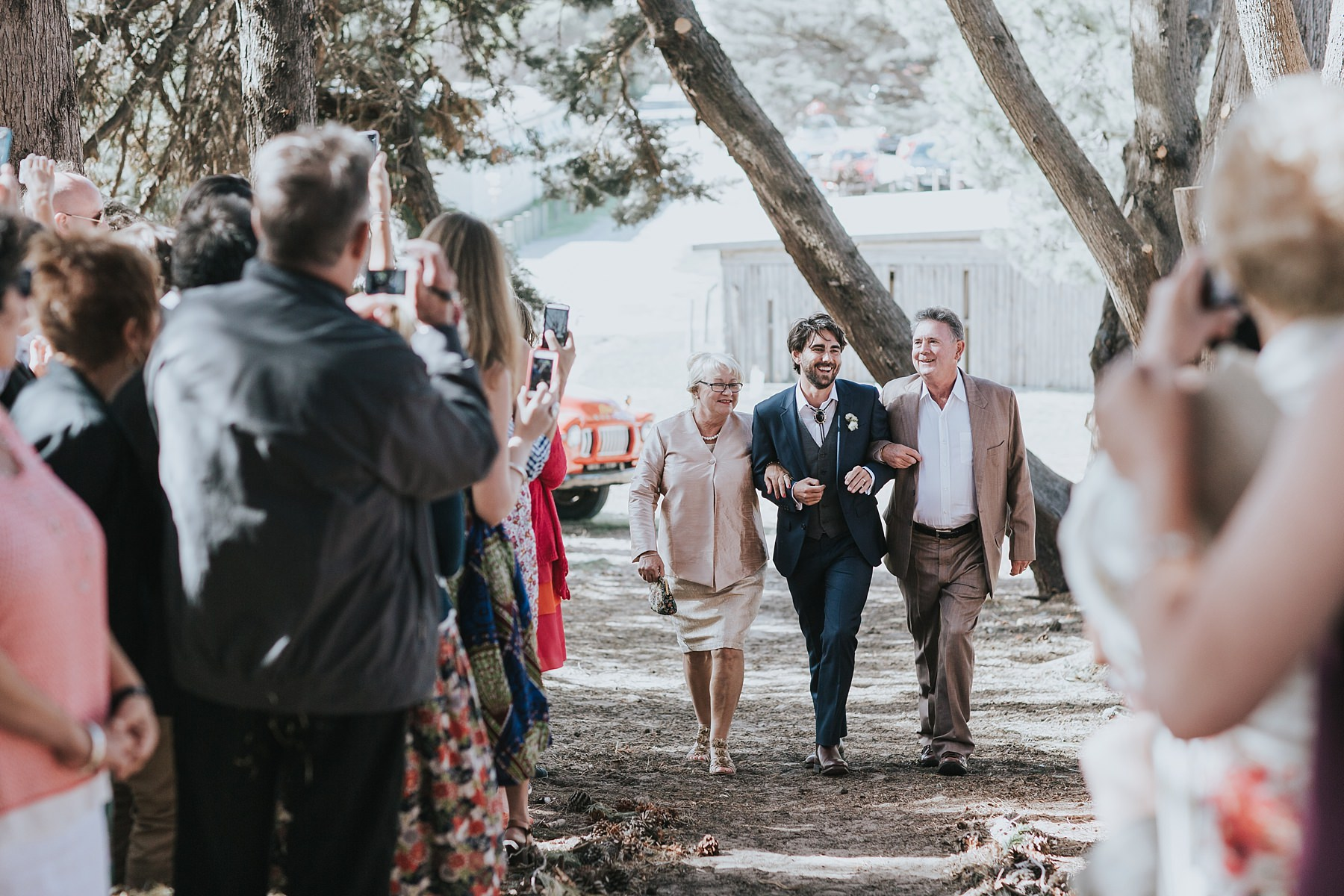 grooms parents walking him down the aisle