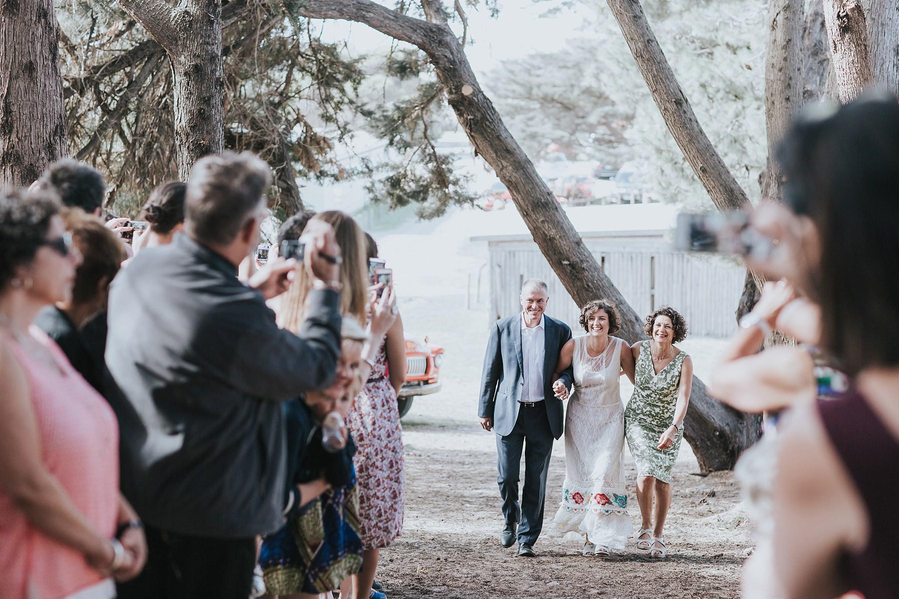 brides parents walking her down the aisle