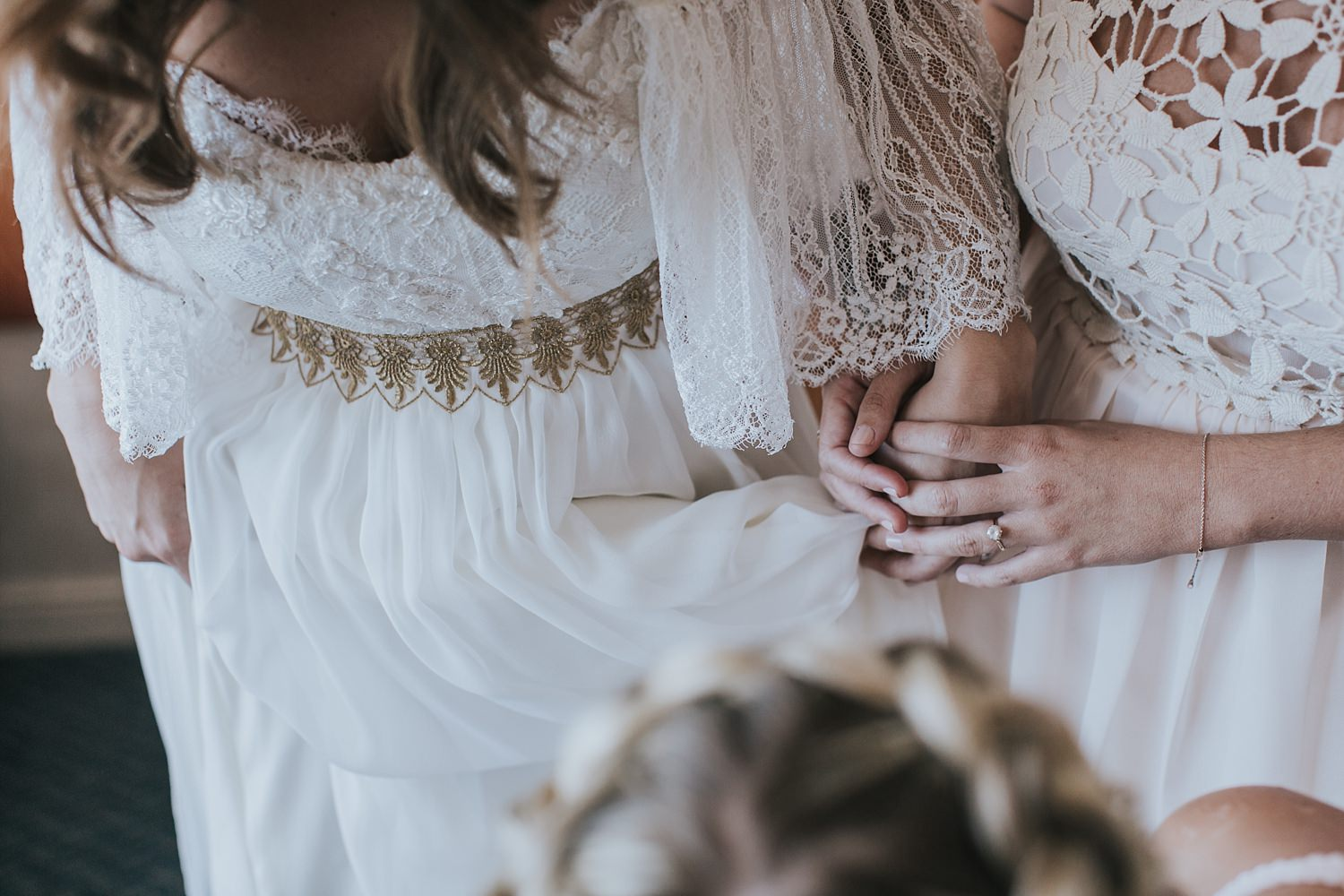 holding hands with her maid of honour during bridal prep