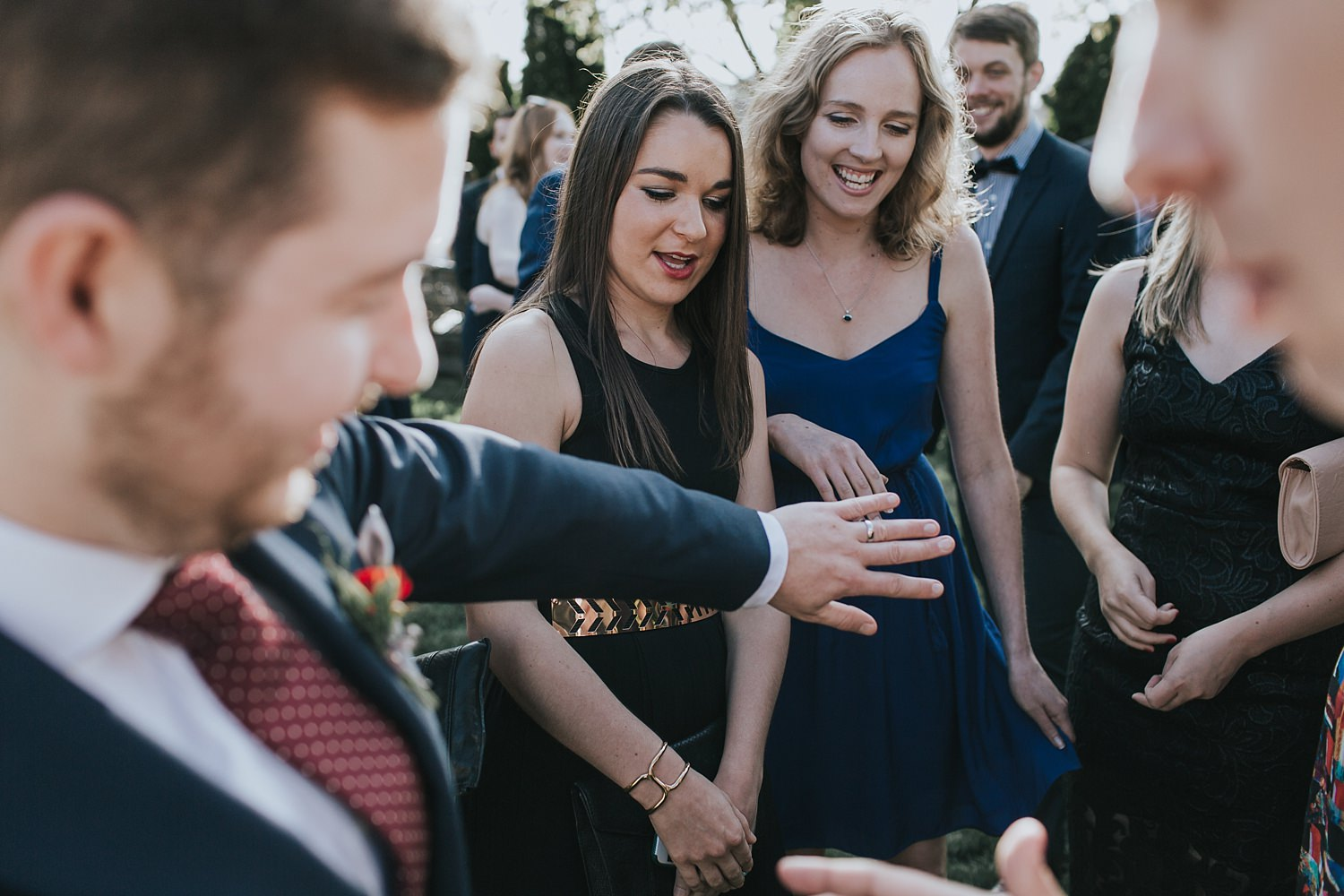 groom shows off his ring to wedding guests