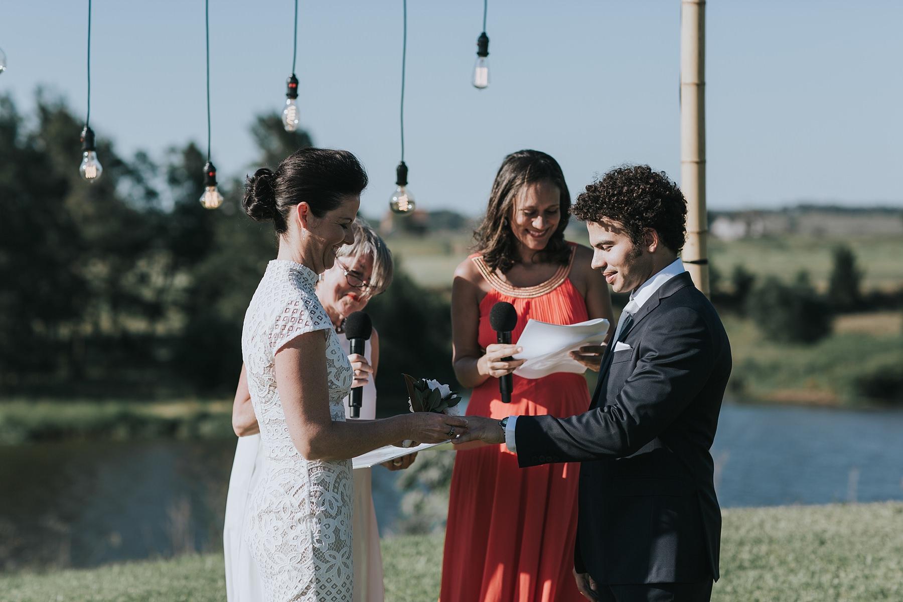 exchanging wedding rings under the arbor at cornwallis house