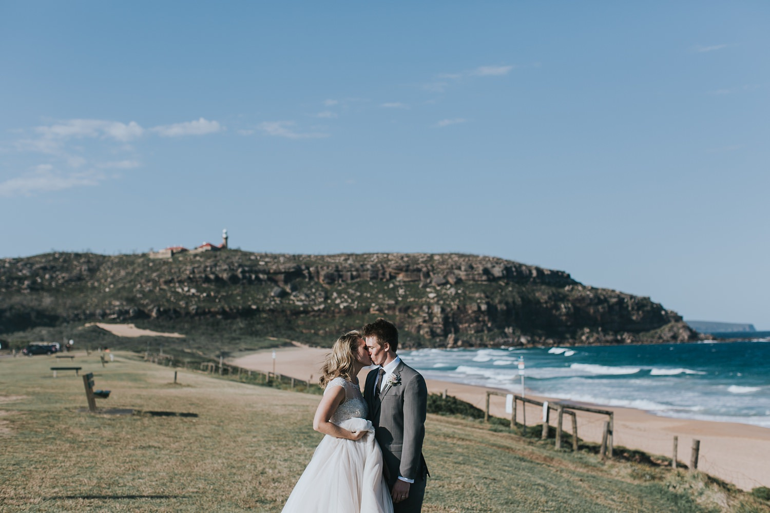bride and groom with palm beach headland behind them