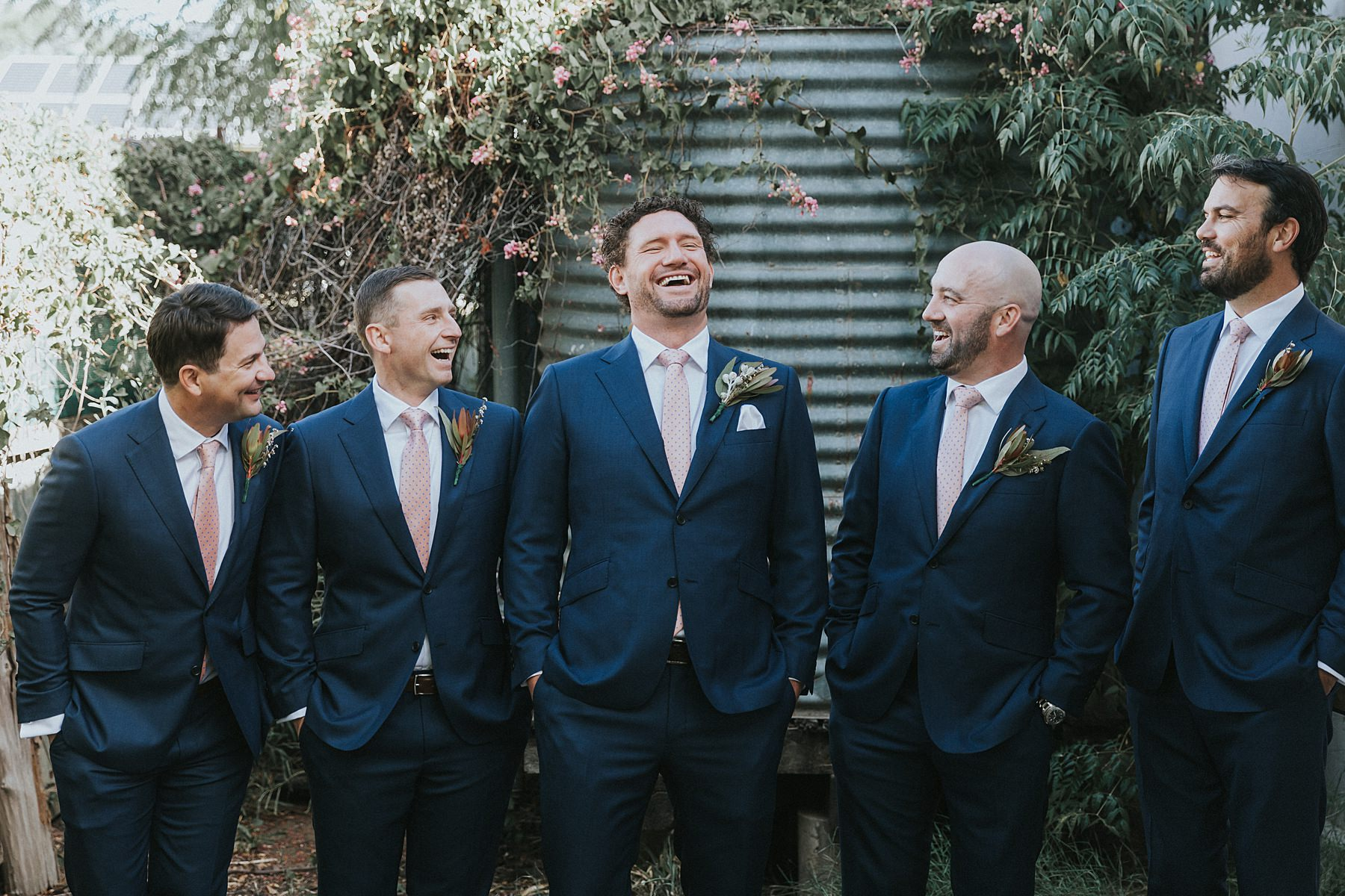groomsmen laughing during groom prep photos