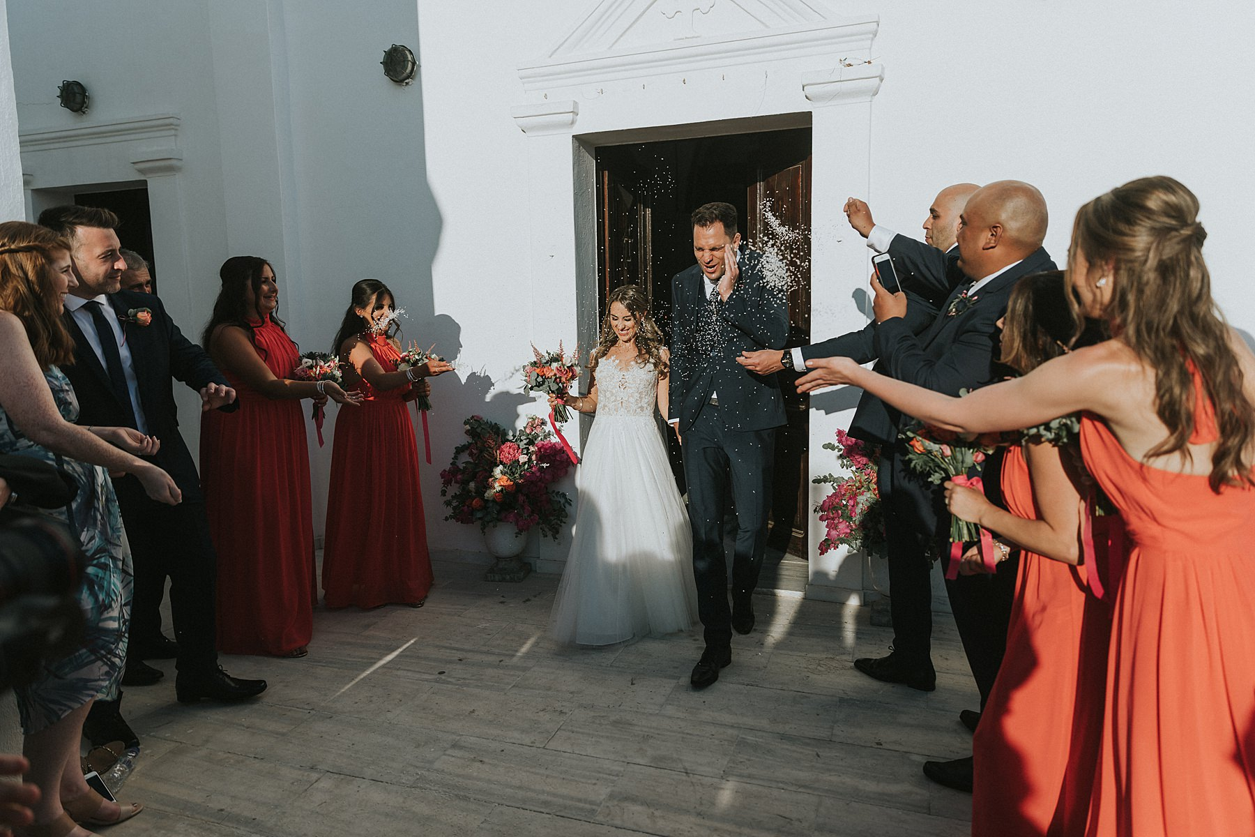 greek orthodox ceremony rice throwing at bride and groom in santorini wedding photography