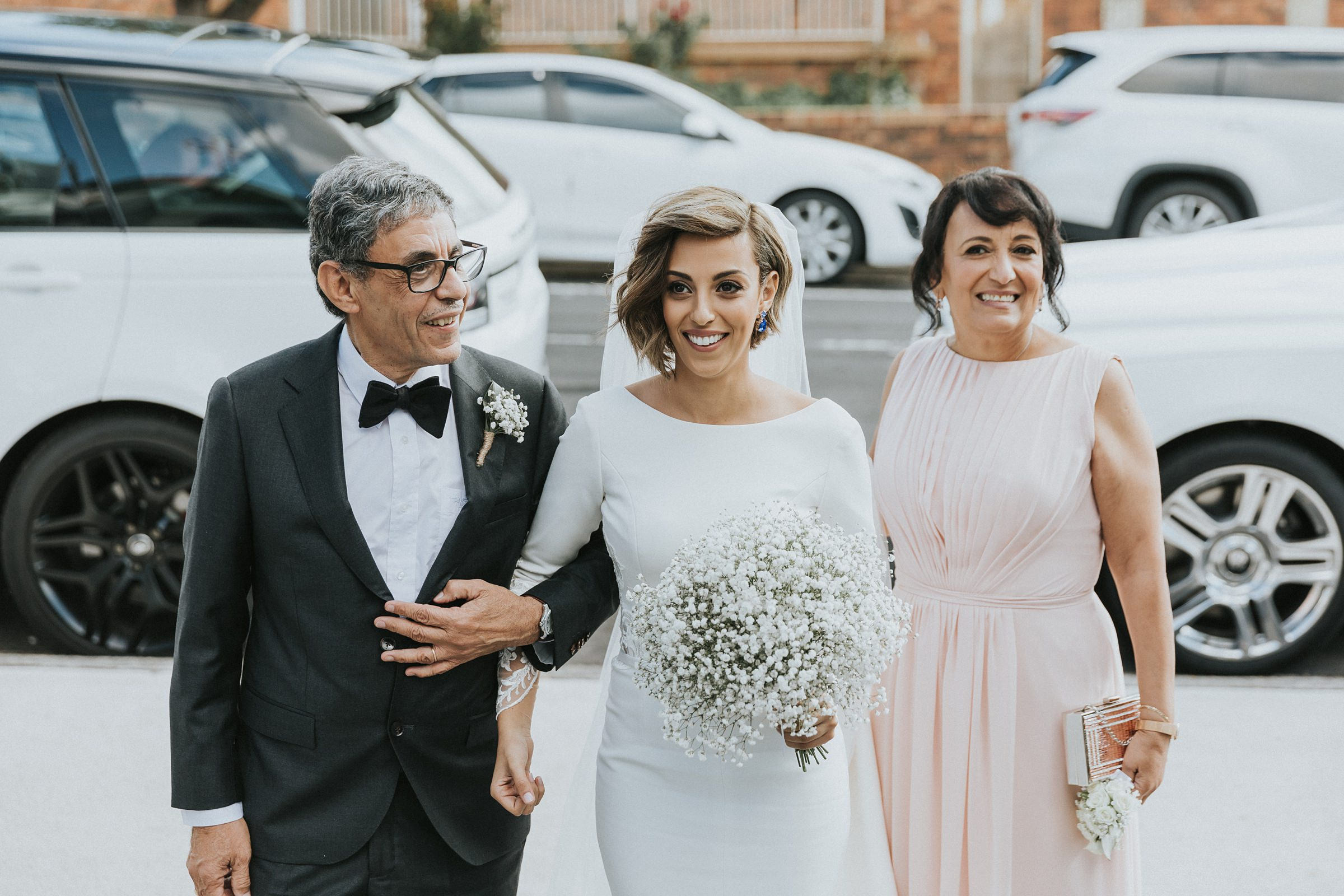 bride with her parents for church wedding photography