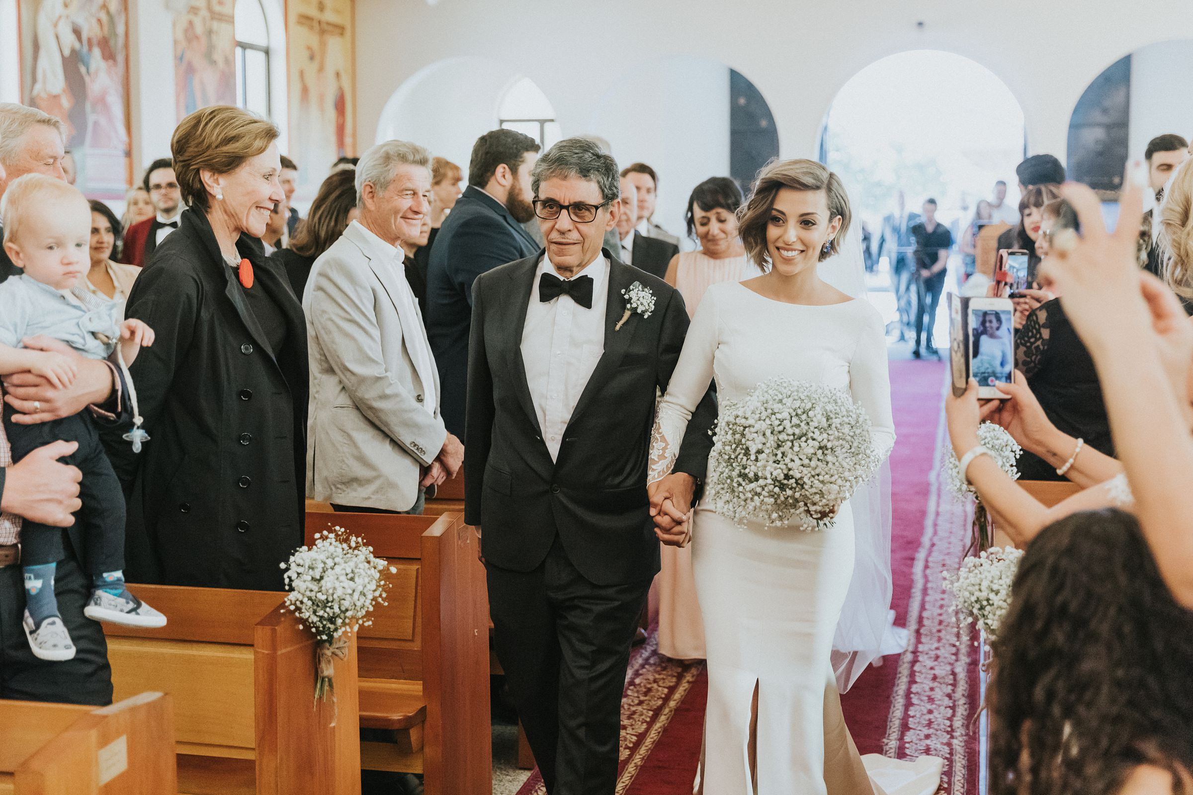 bride and her father walk down the aisle during wedding ceremony