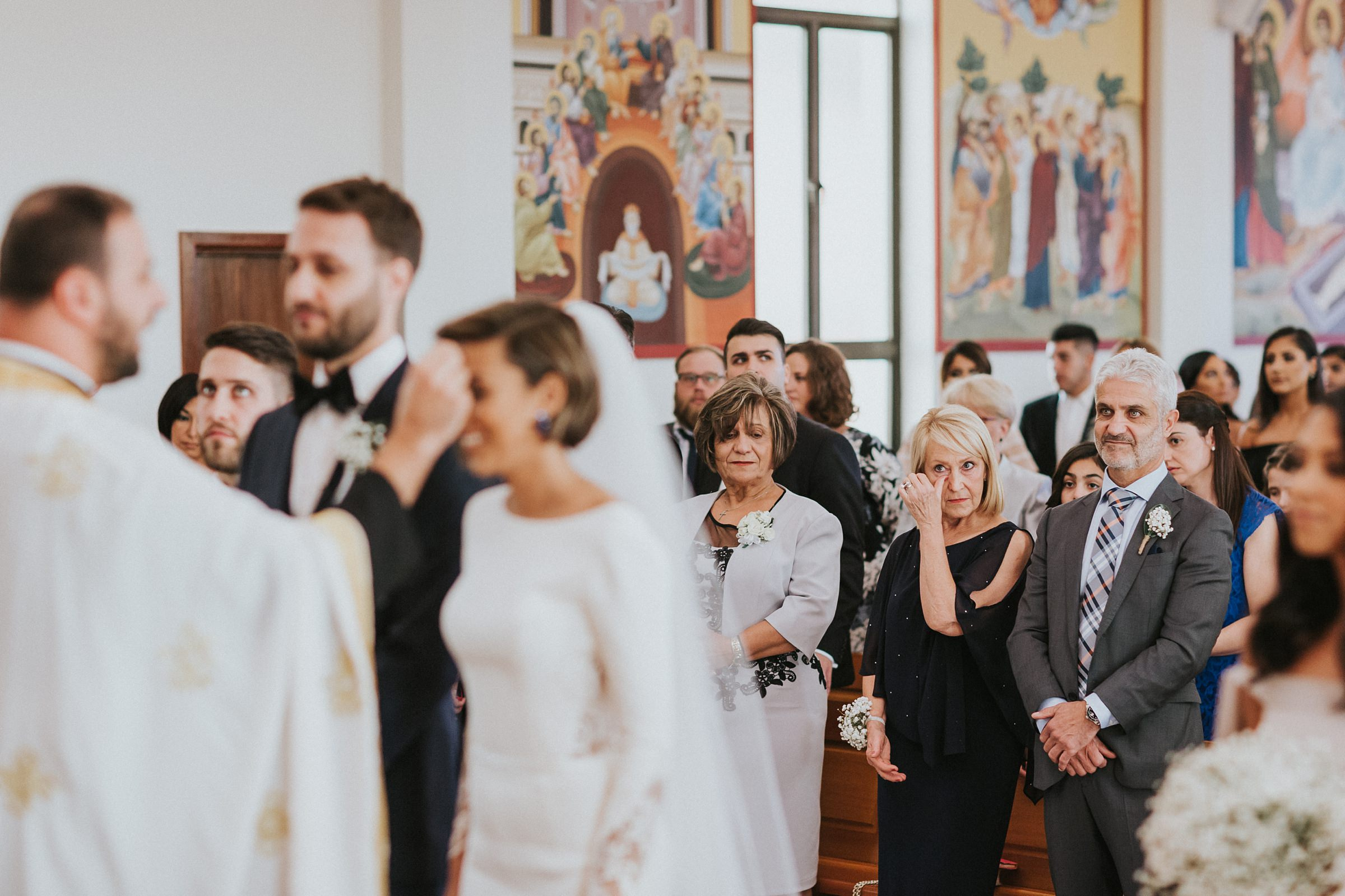 mother of groom wipes away a tear during wedding photography
