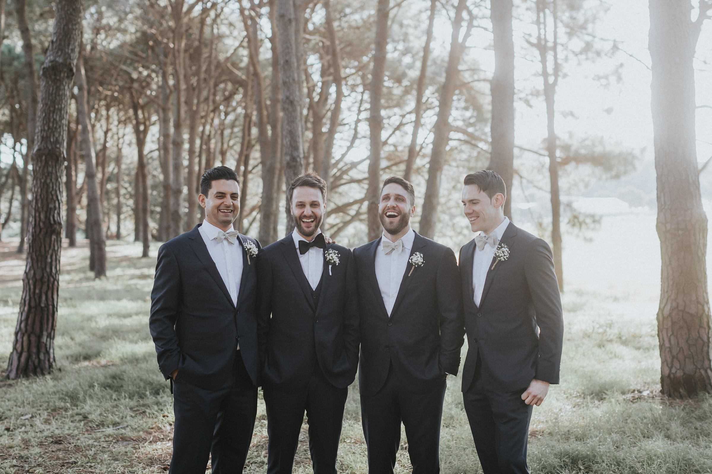 groomsmen laughing in the pine groves during portraits in sydney