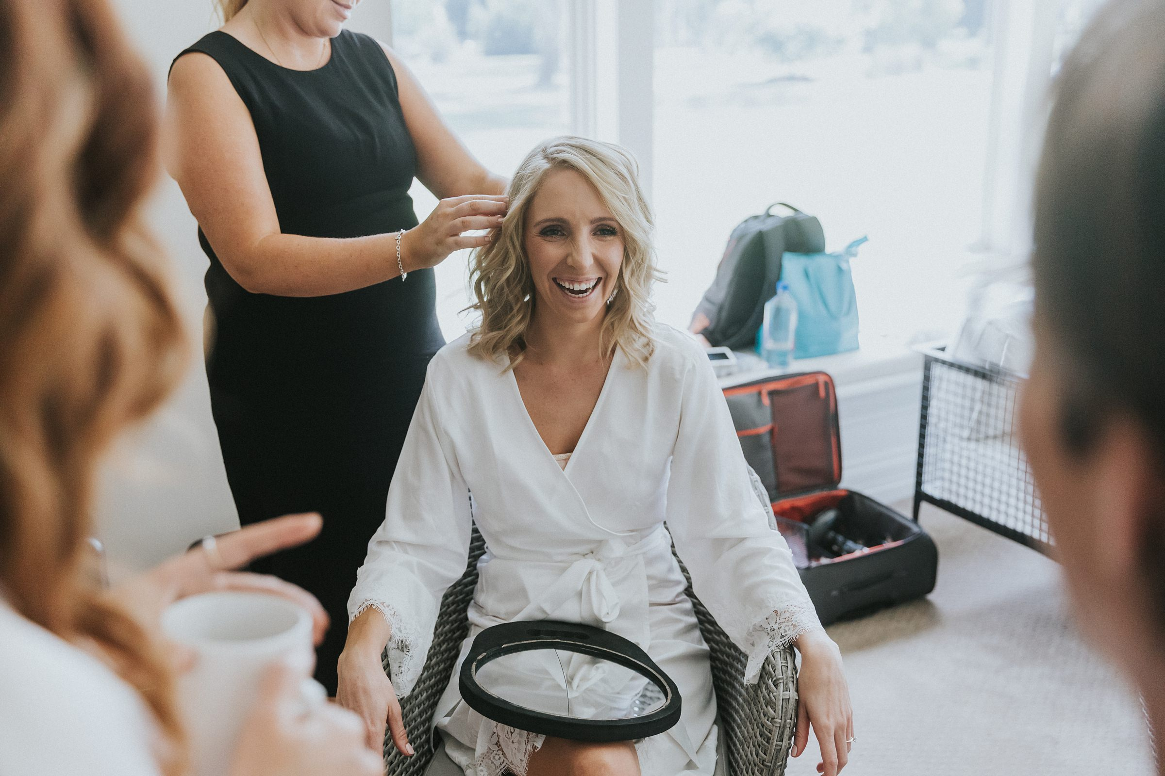 bride getting her hair done during bridal prep