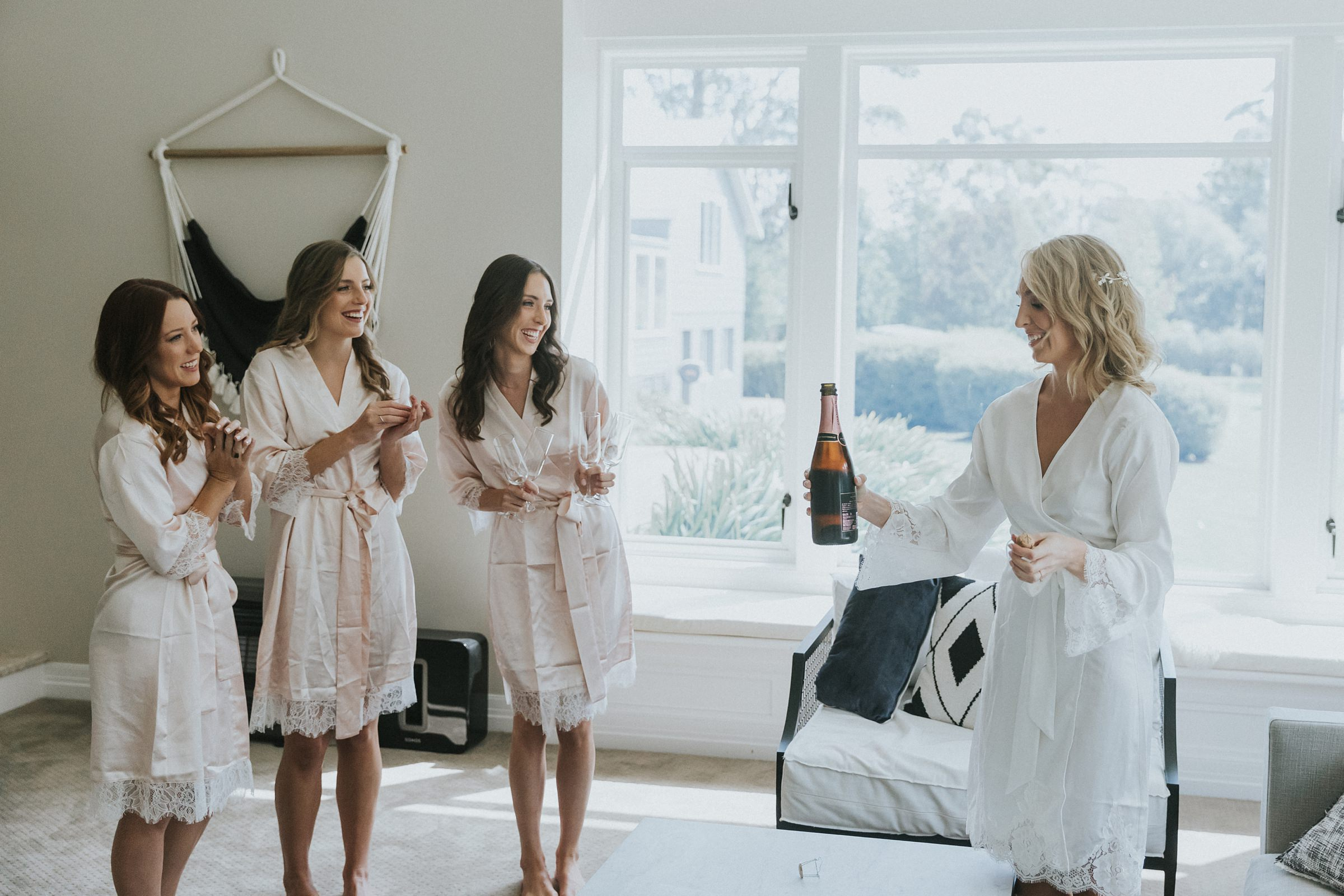 bride popping a bottle of champagne on her wedding morning
