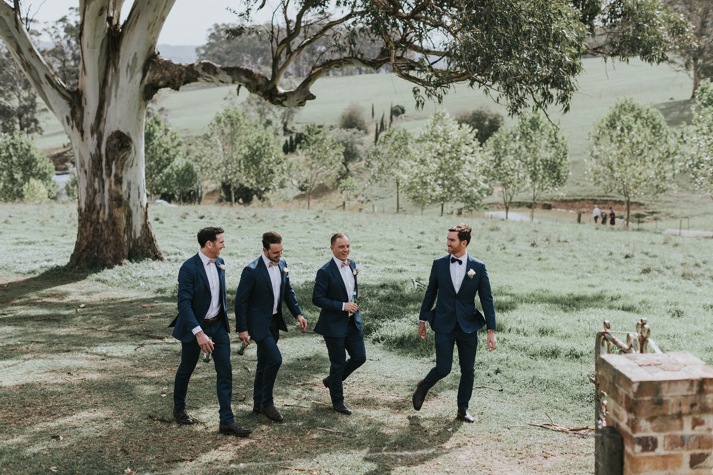 groom and groomsmen walk down to their wedding ceremony
