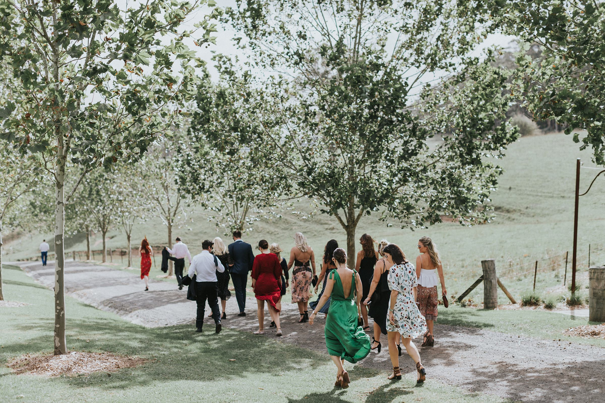 guests walk to the wedding ceremony site near the lake at mali brae farm