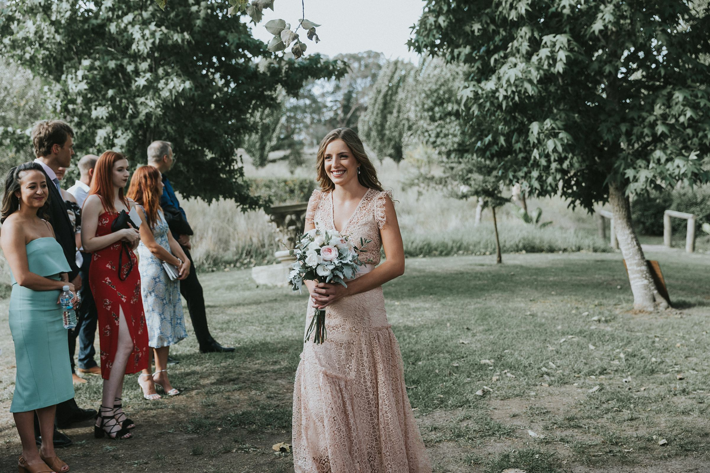 bridesmaid smiles as she walks down the aisle at mali brae