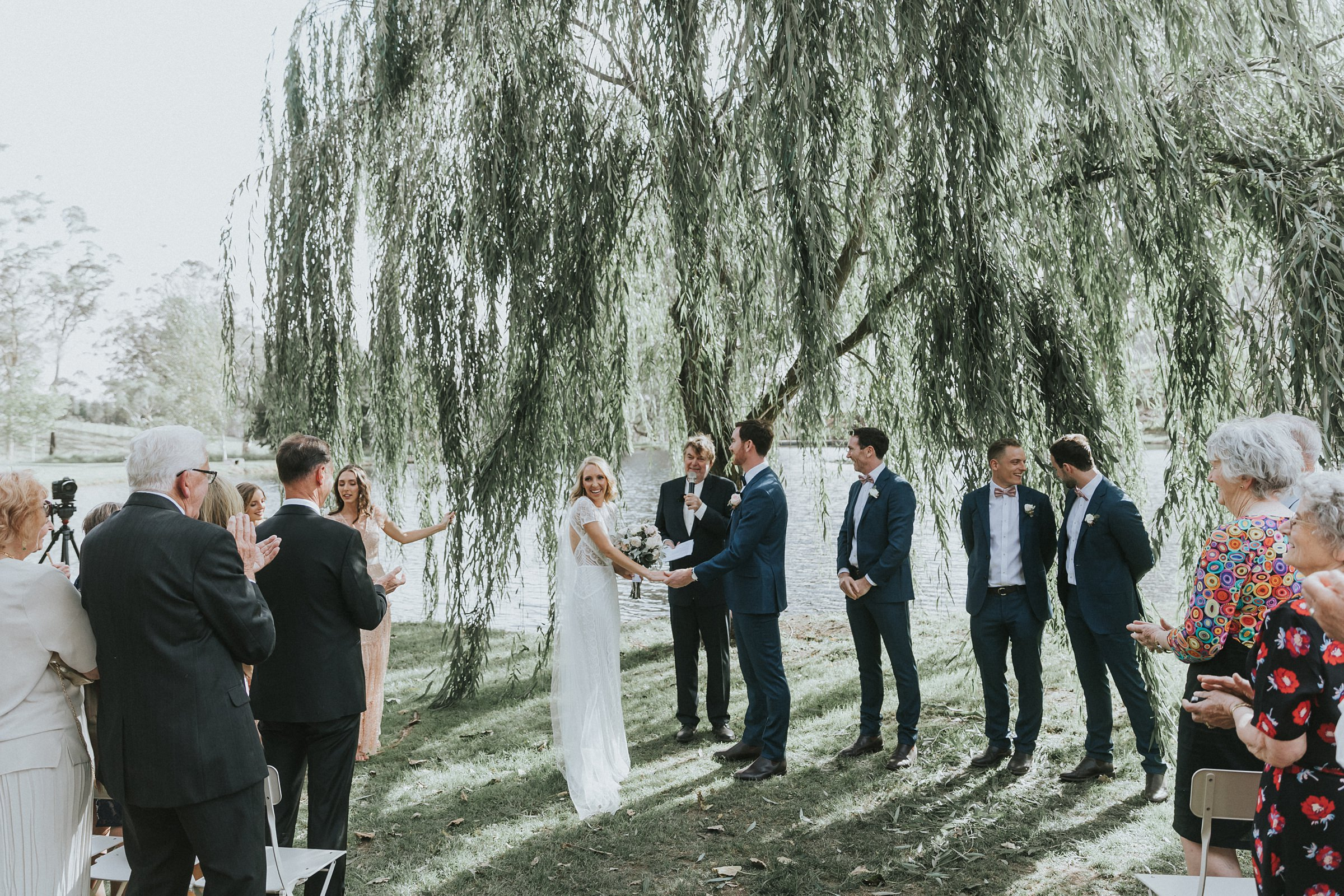 wedding ceremony under the willow tree by the lake at mali brae farm