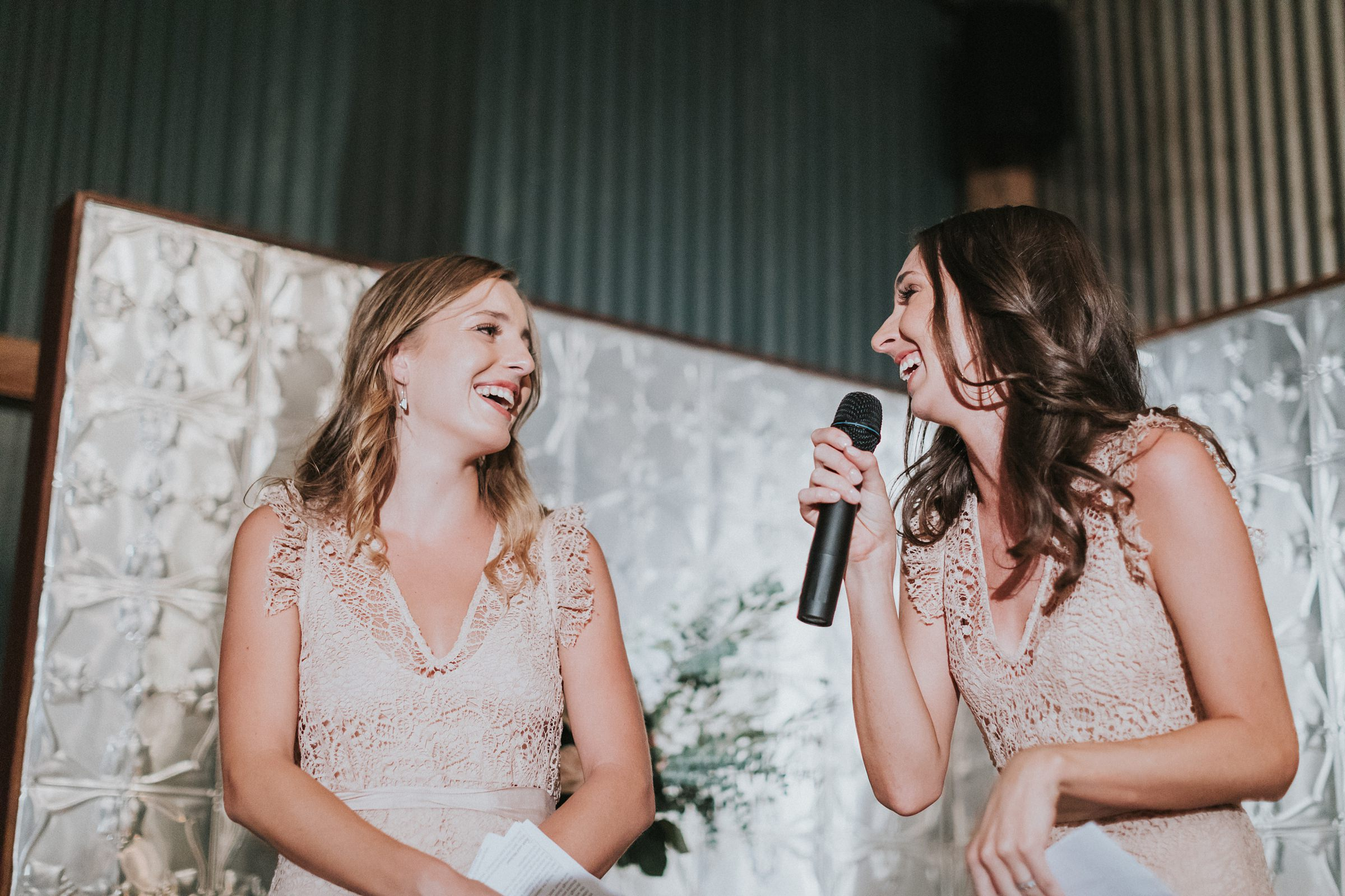 sisters of the bride speak at wedding reception