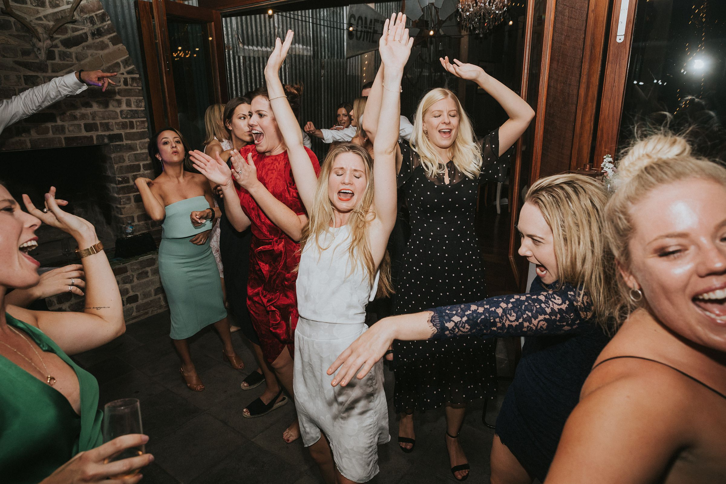 crazy dancing on the dance floor of a farm wedding
