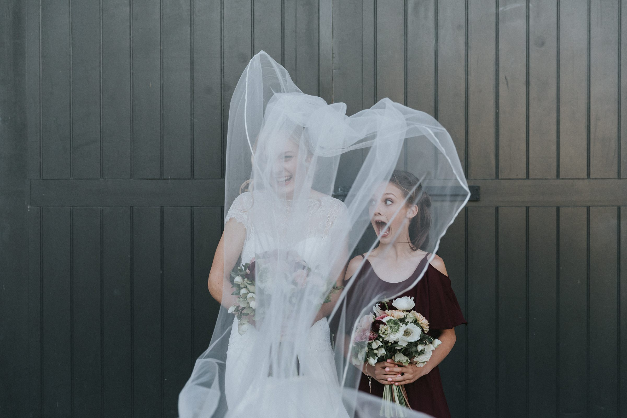 brides sister stunned by the veil flying in the wind