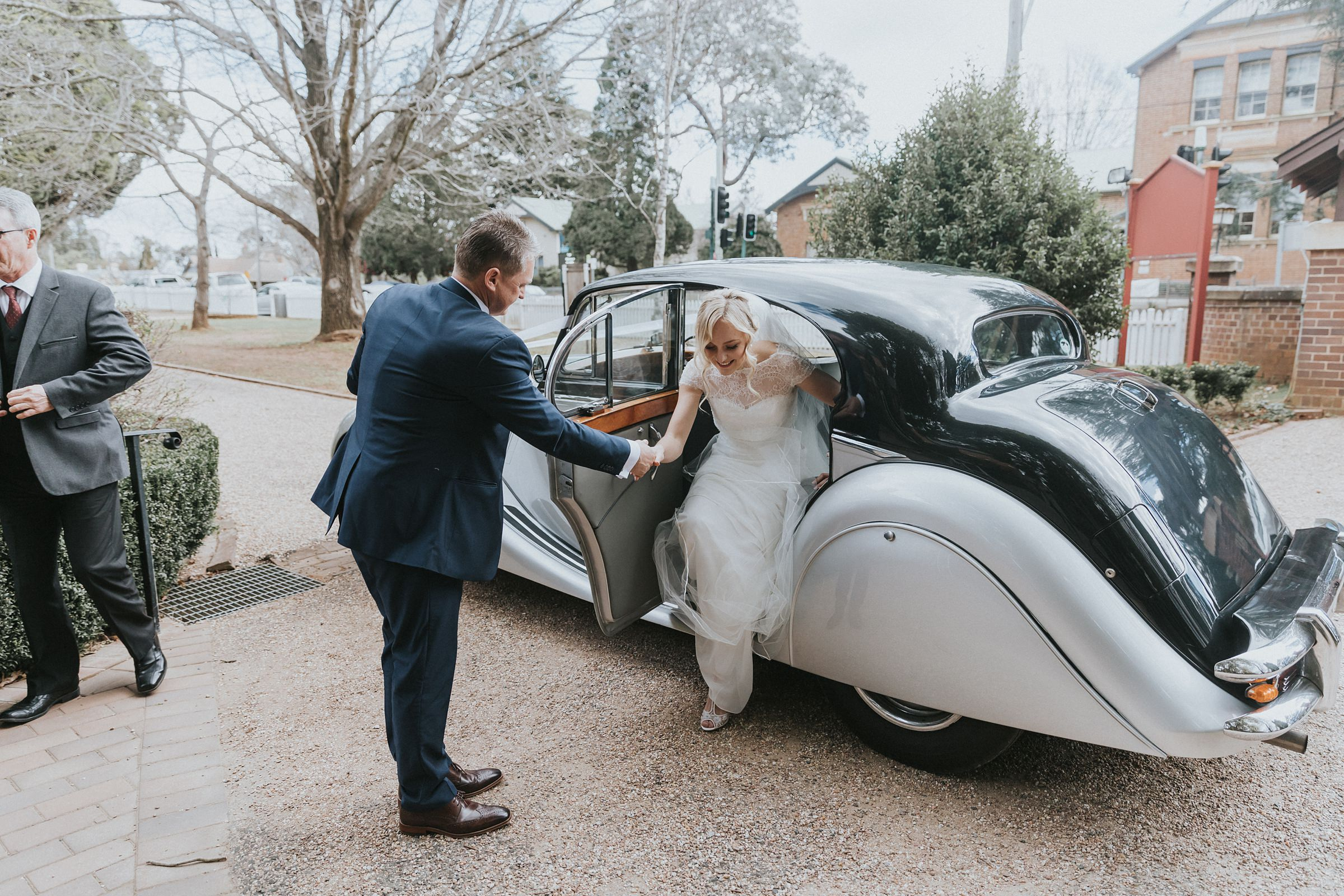 bride steps out from vintage bridal car in bowral