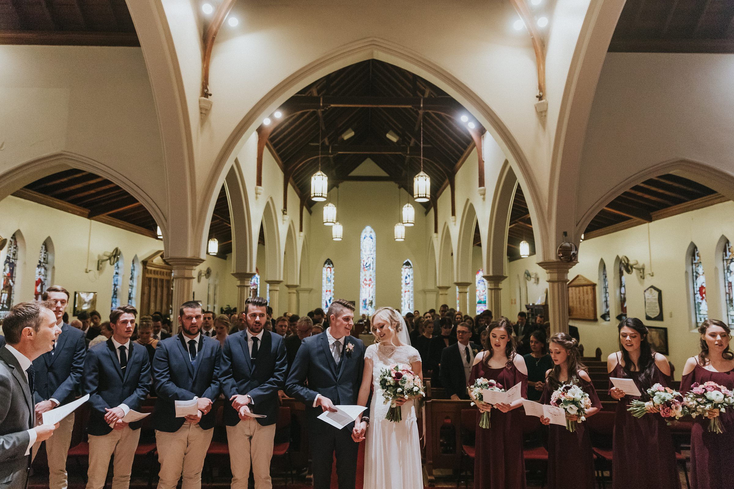 bride and groom sing hymns during wedding ceremony at st jude's anglican church in bowral