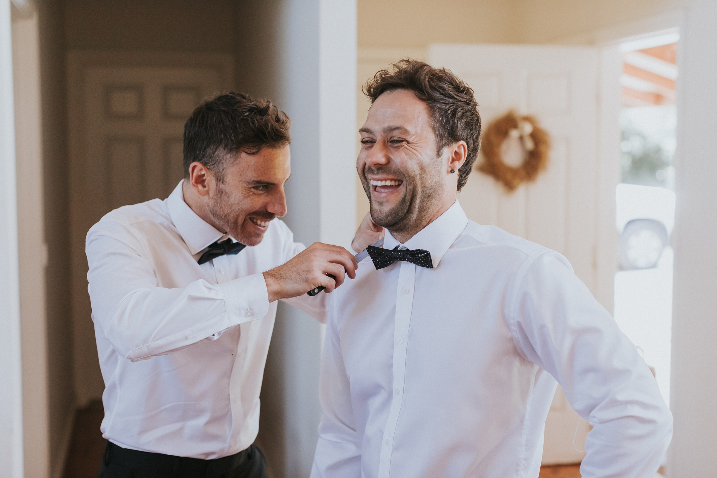groom gets help putting on his bow tie at melross farm wedding