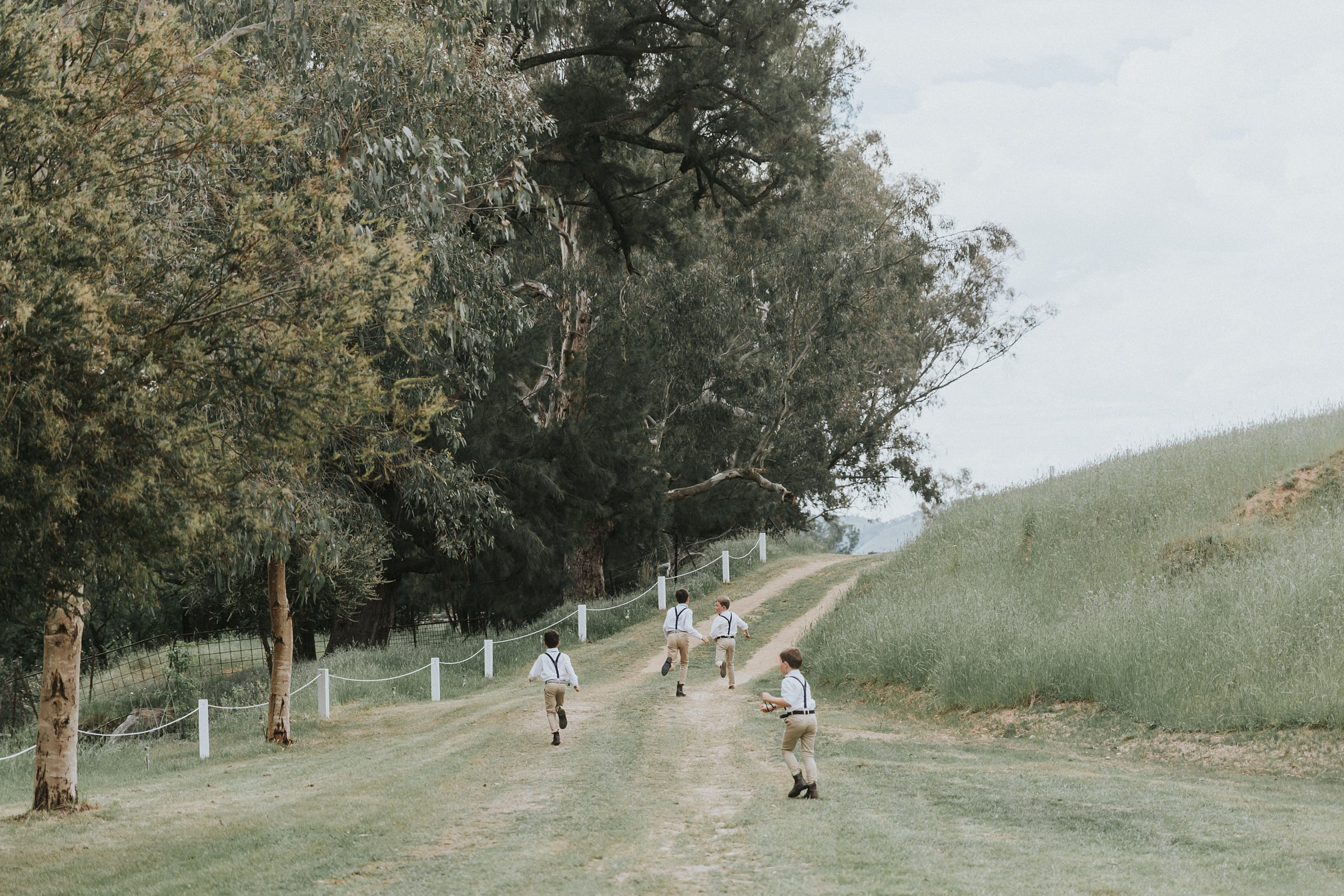 page boys running to the guests at the river in tumut