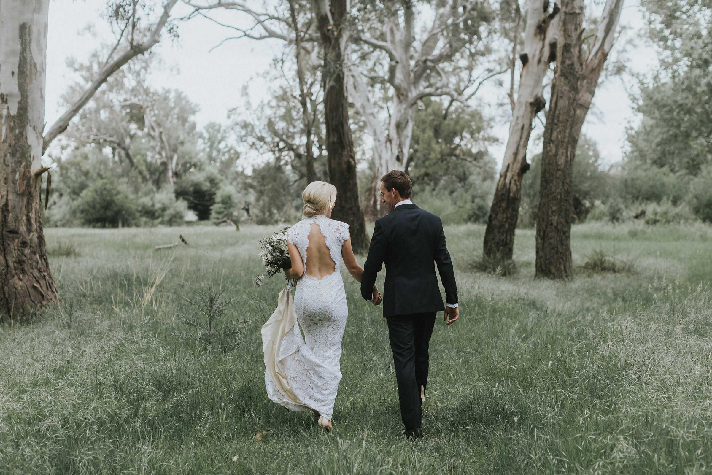 bride and groom walking together in long grass in country new south wales