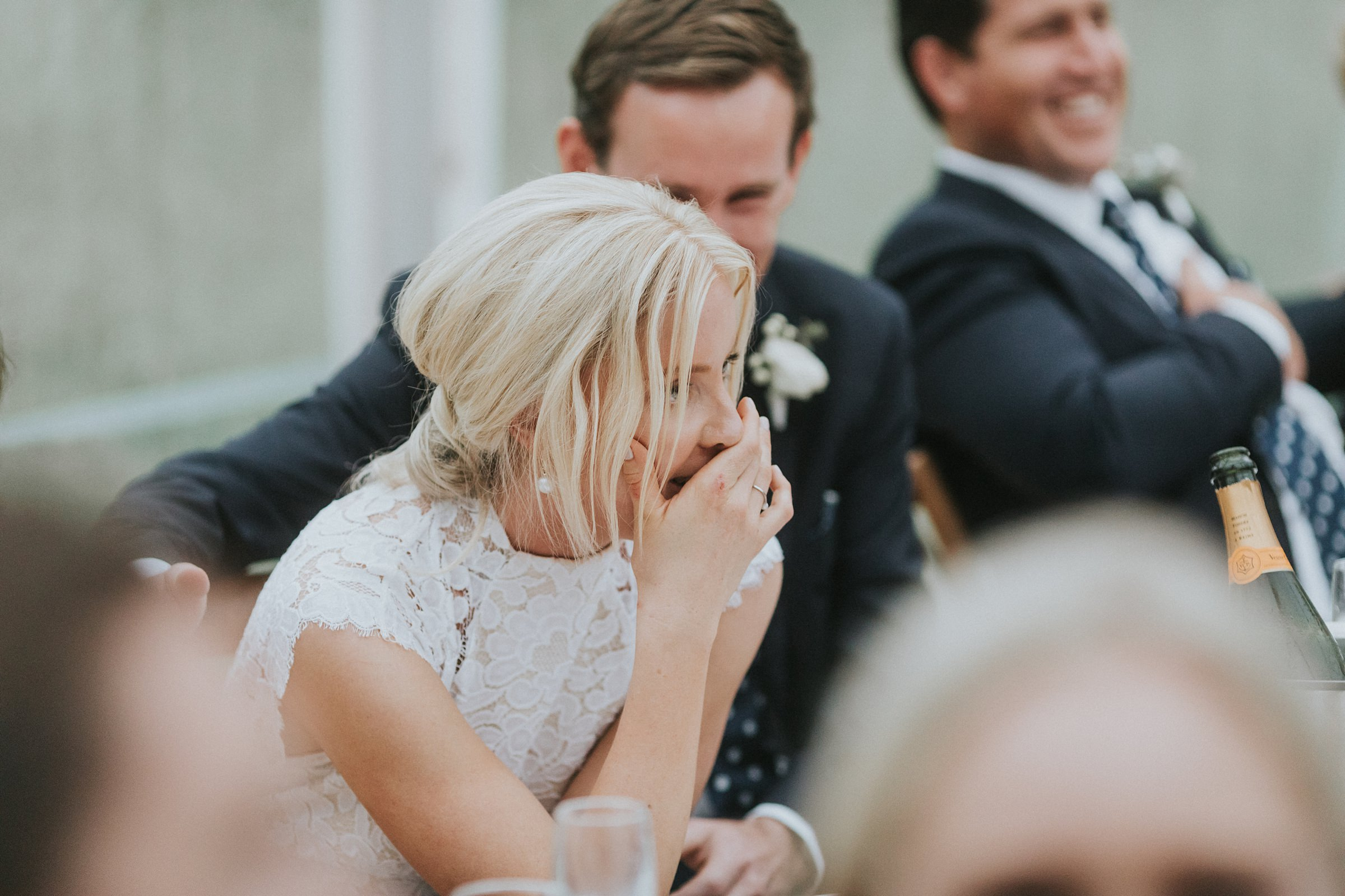 bride enjoying the speeches during wedding reception
