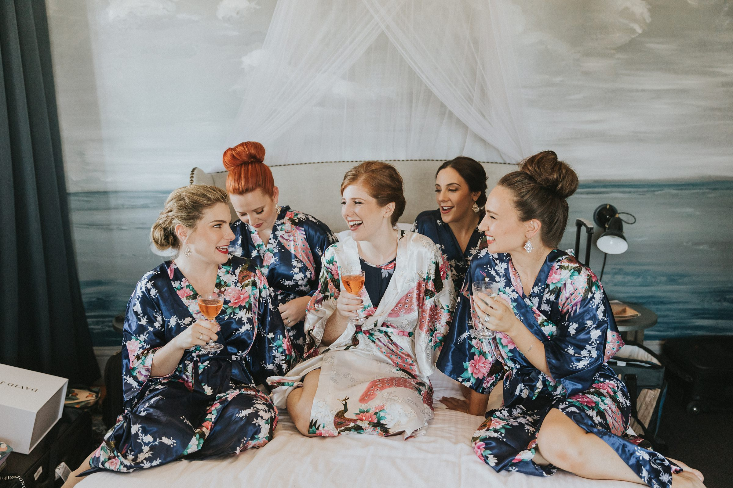 bride with bridesmaids on bed drinking champagne on wedding morning