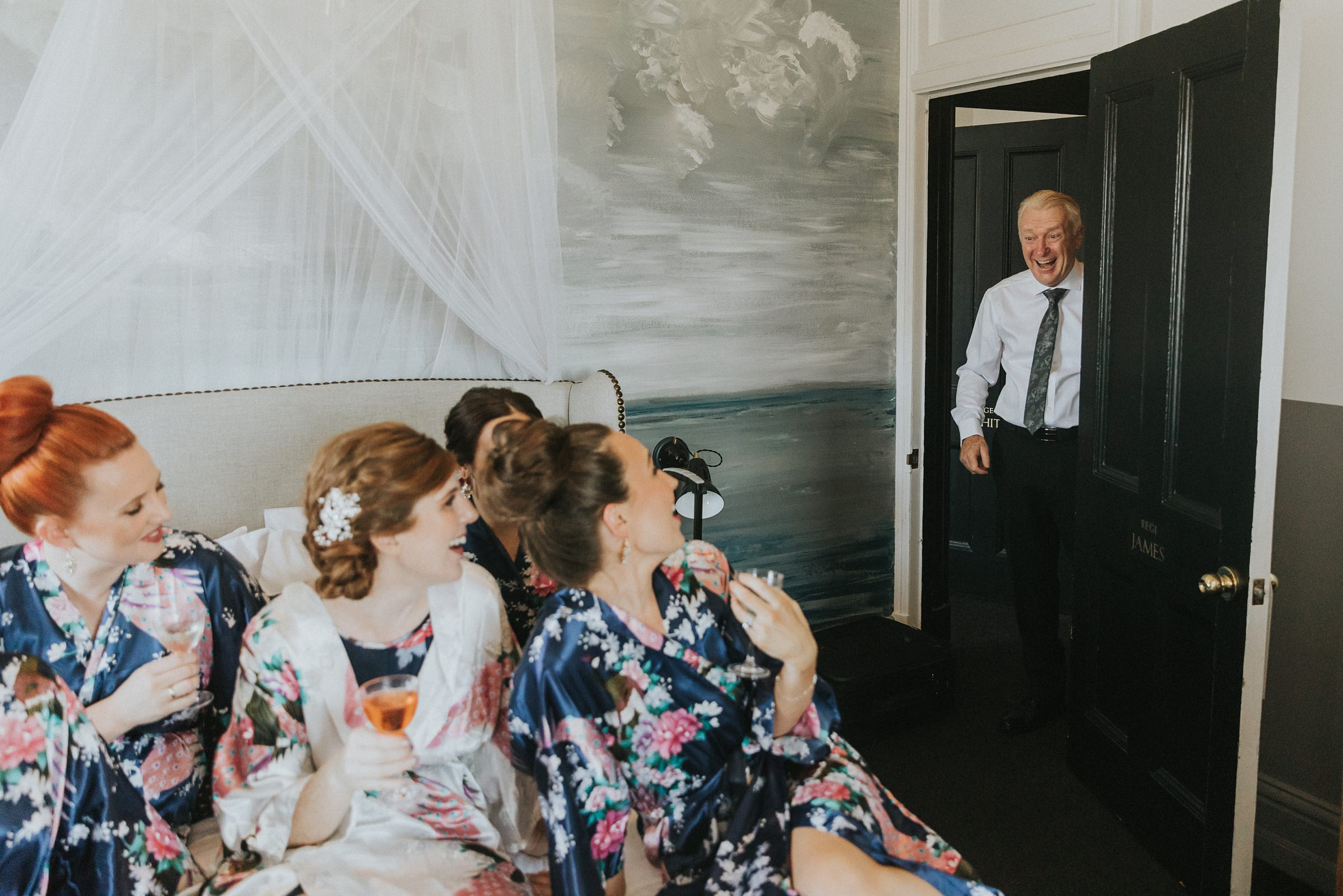 bride's father surprised by the bridesmaids on the bed during wedding preparations