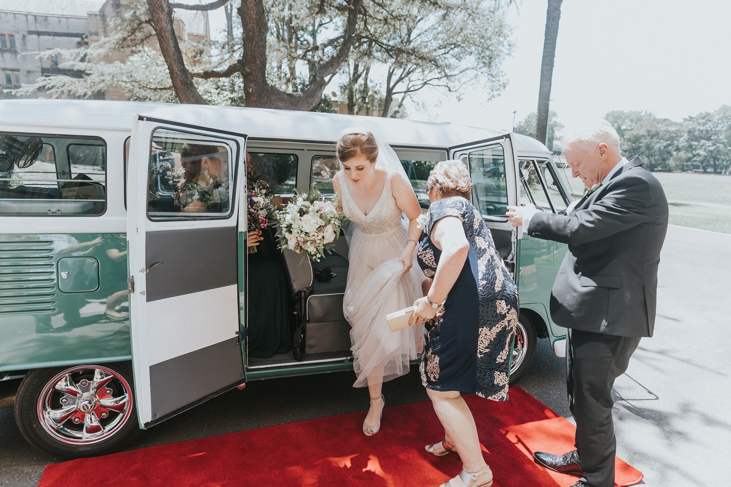 bride steps out from green kombi on her wedding day