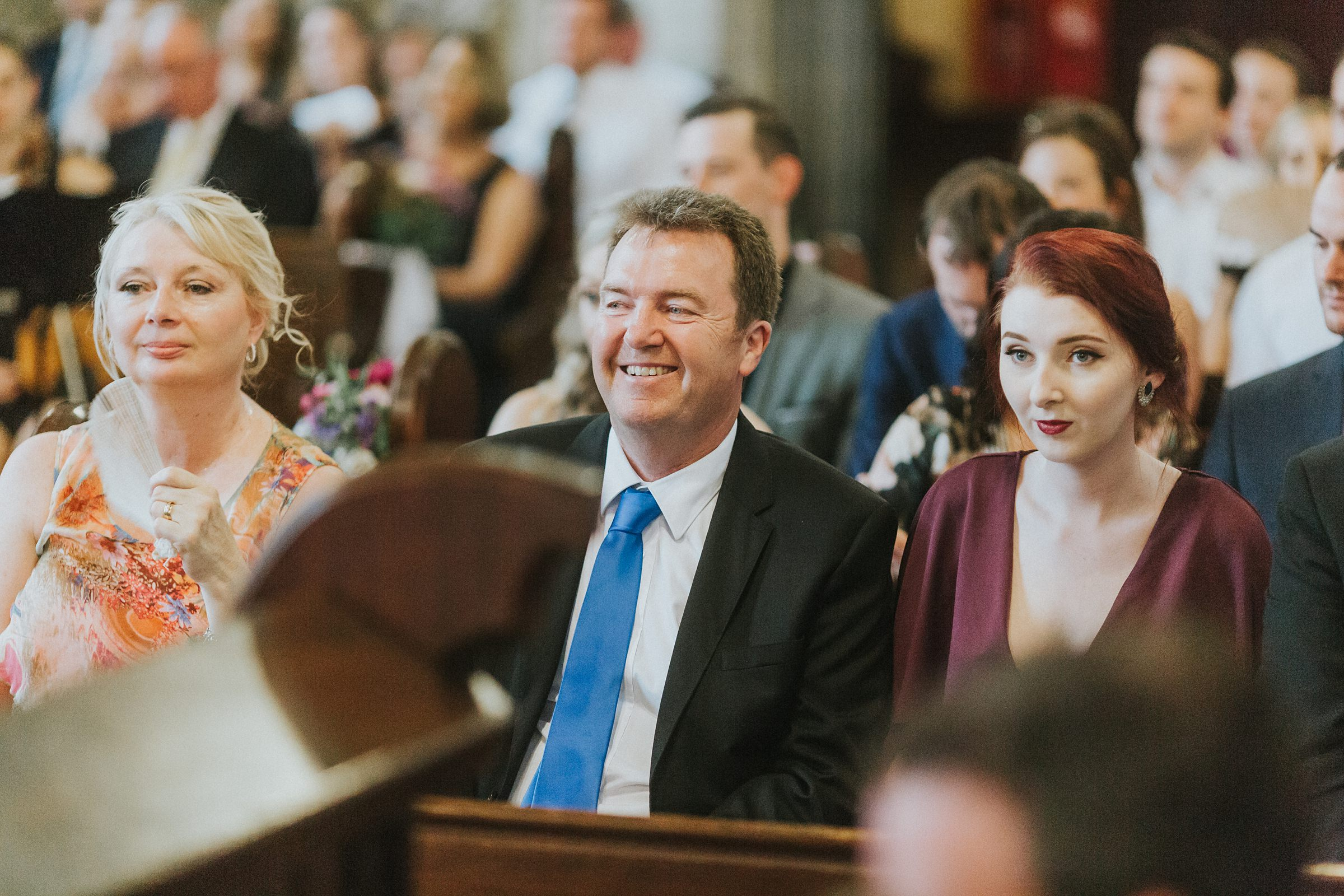 guests laughing during wedding ceremony at st john's college chapel