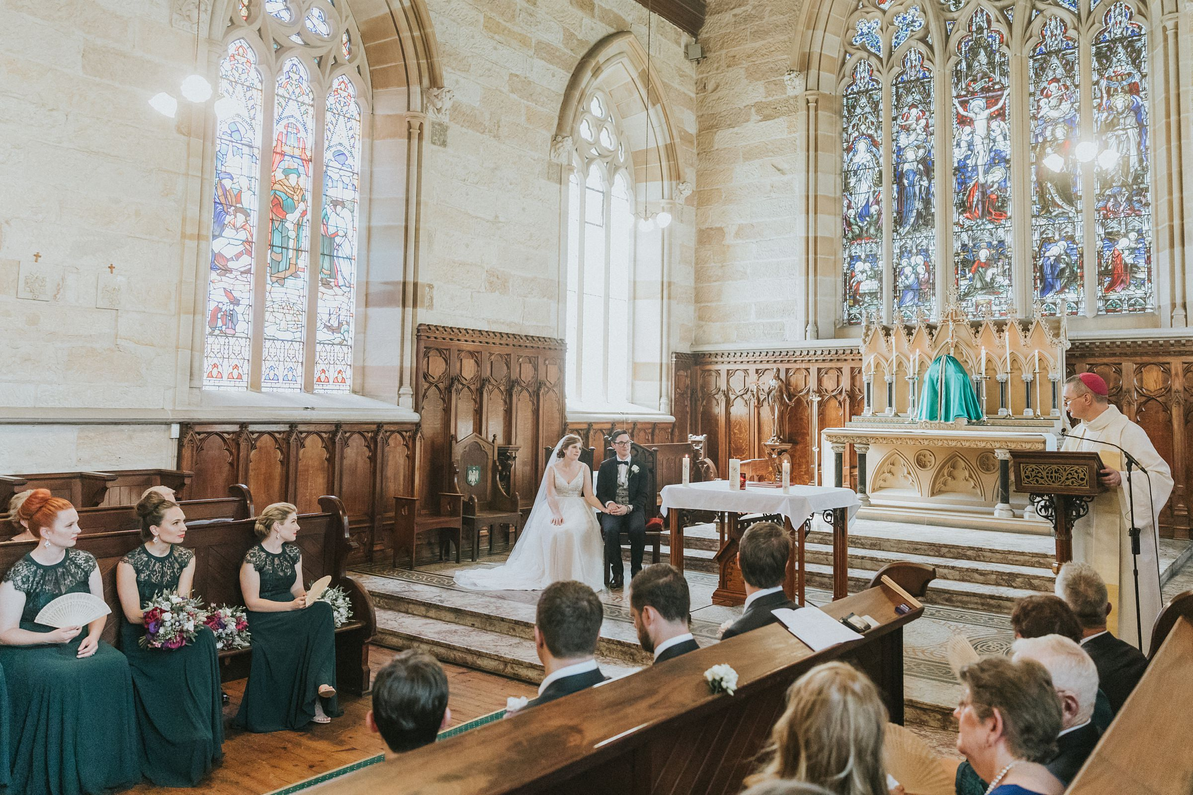 bride and groom seated during wedding ceremony in catholic church