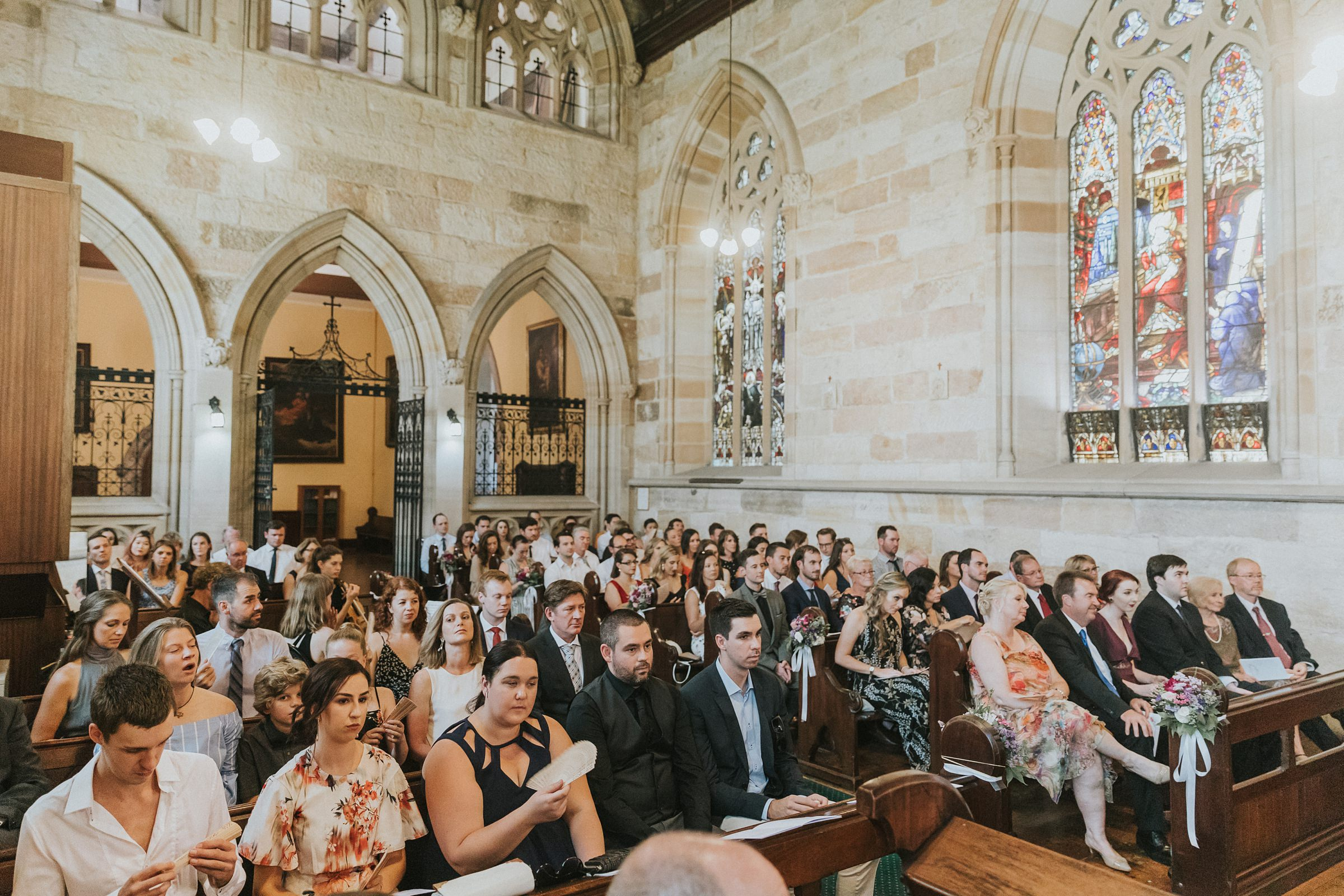 wedding guests in sandstone church for wedding ceremony