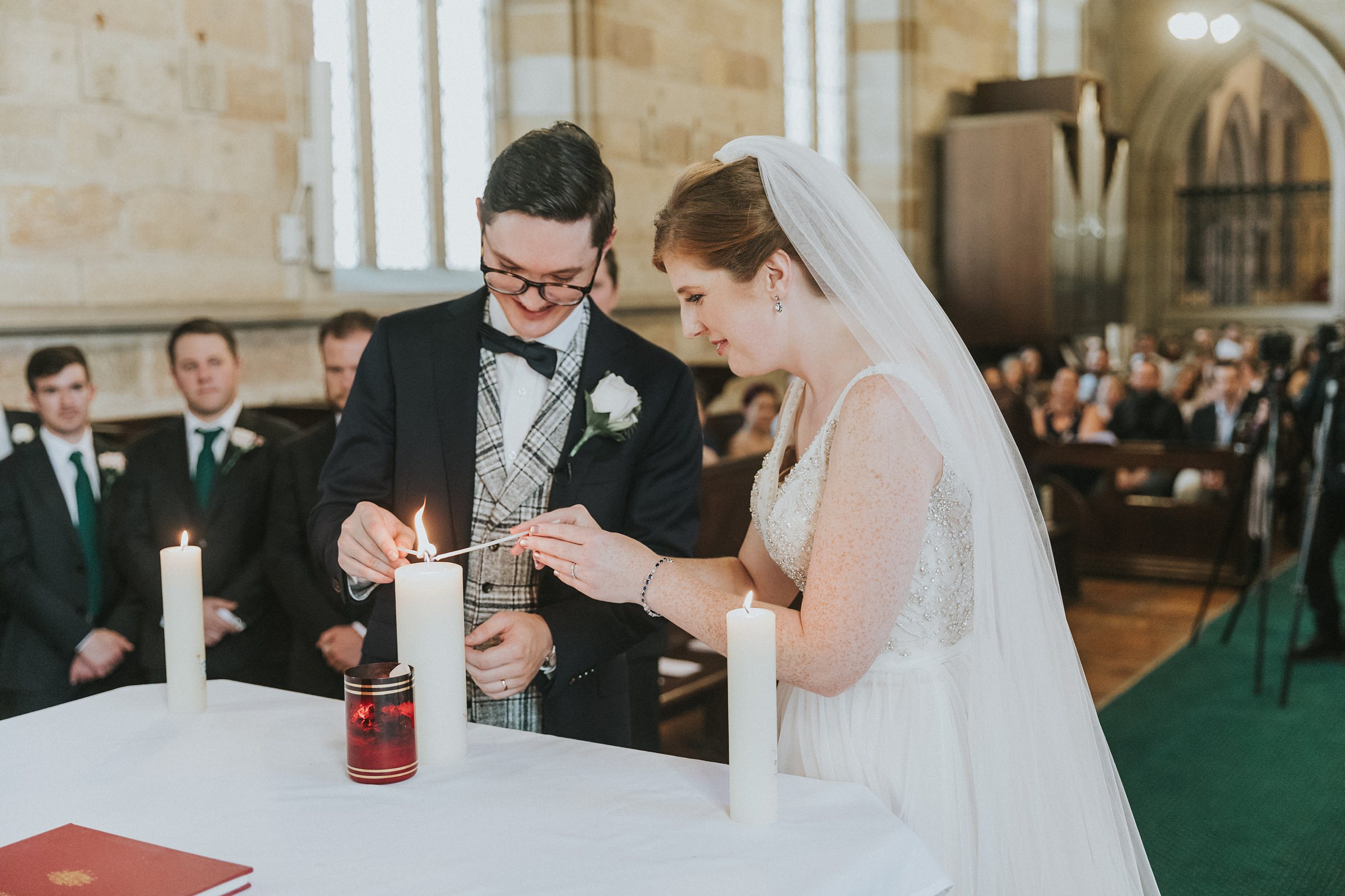 lighting their marriage candle during catholic wedding service